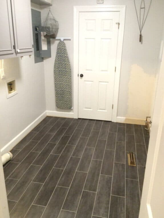 Vintage Inspired Laundry Room Makeover - removing water heaters and installing floors