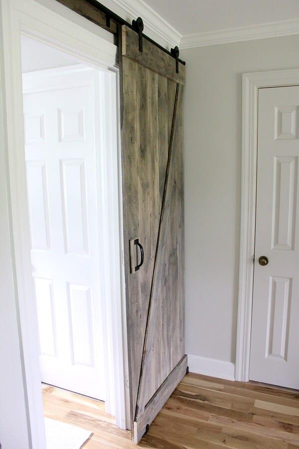 Simple DIY Barn door tutorial - Jen @ Noting Grace shares how easily it is to switch out a builder grade door with a sliding barn door.