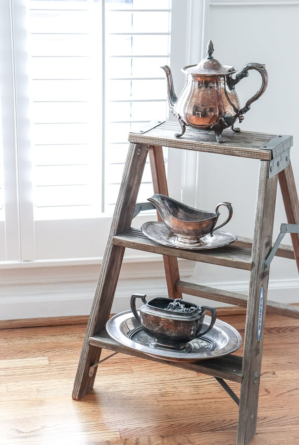 Tarnished silver sitting on a rickety step ladder is a great piece to put in your dining room corner.