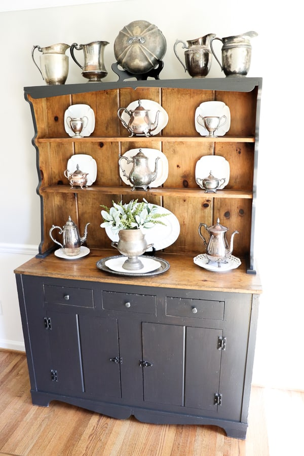 I love when furniture tells a story that takes you back in time. Our updated hutch is a classic vintage piece. This is the third version and I'm loving the classic painted gray hutch complete with all my tarnished silver!