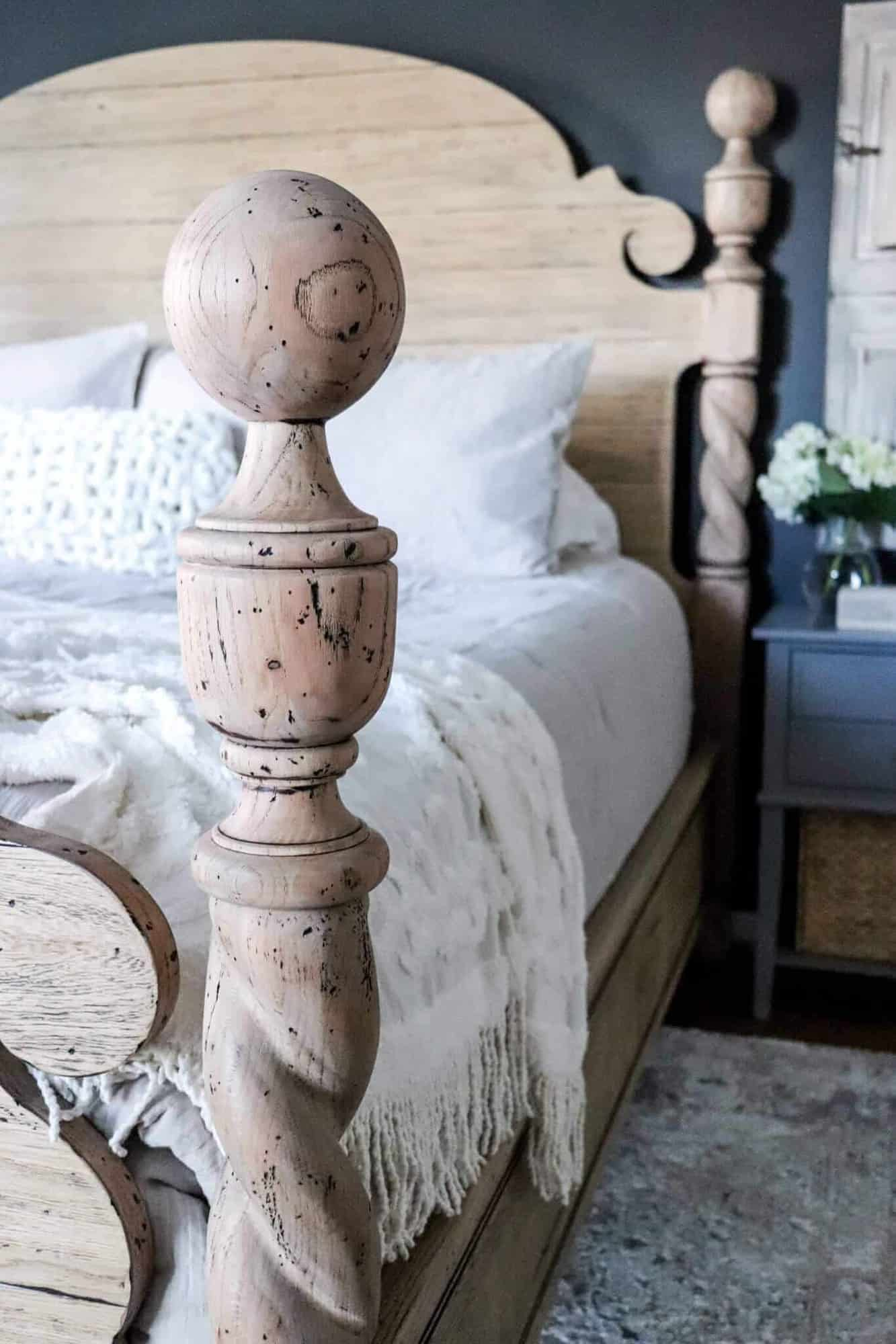 Wooden four post bed with a black accent wall.