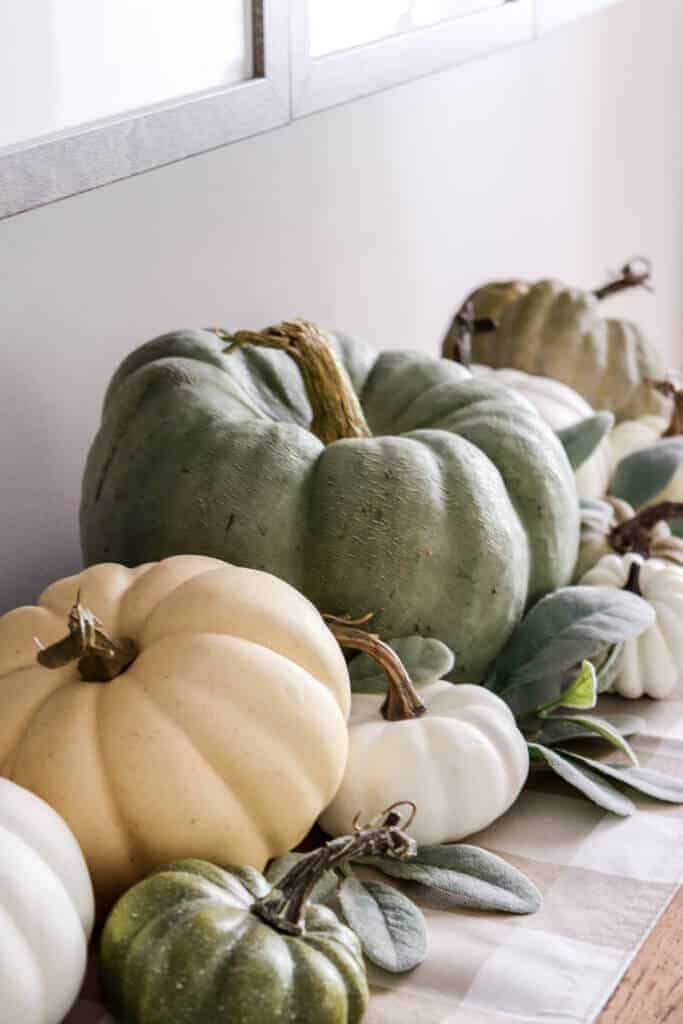 Heirloom pumpkins stacked and gathered on a tabletop.