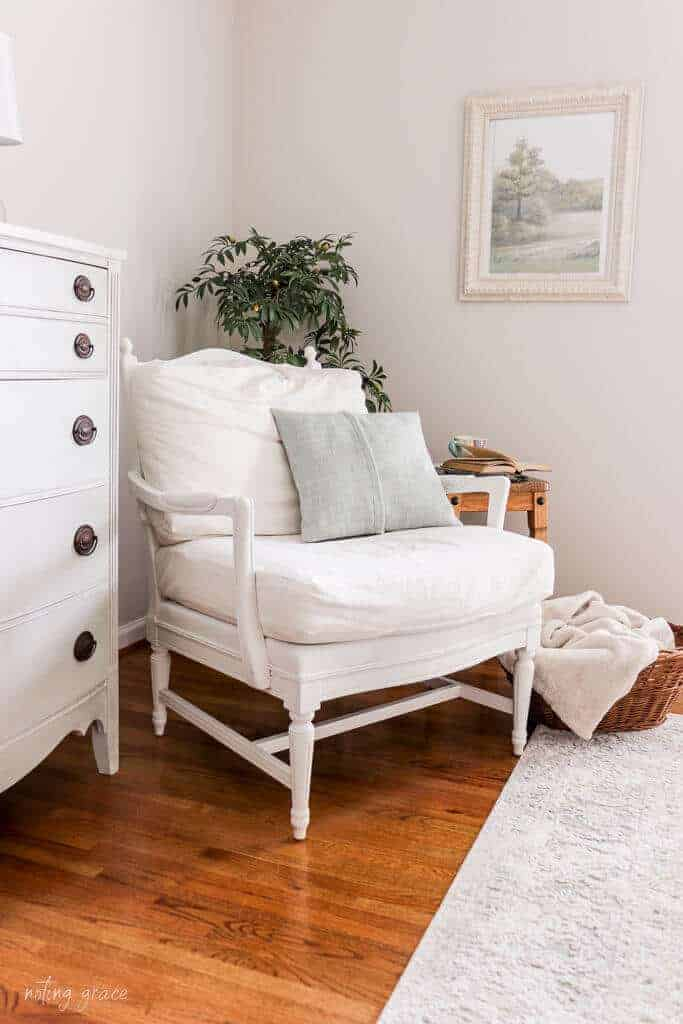 White arm chair with blue pillow sitting next to a soft blue painted dresser.