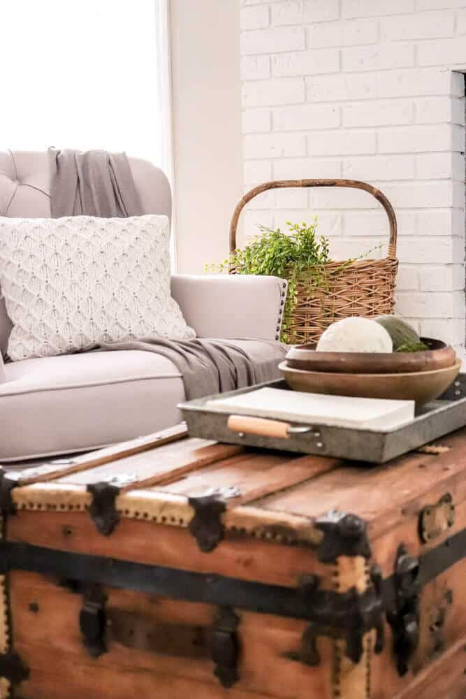 vintage trunk in front of tufted chair next to a fireplace