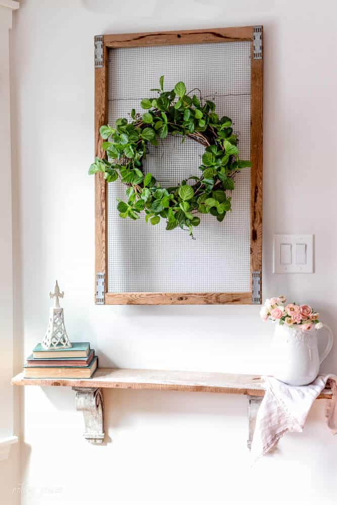 Shelf with architectural wall art. A tulip crate with grapevine wreath wrapped with spring garland