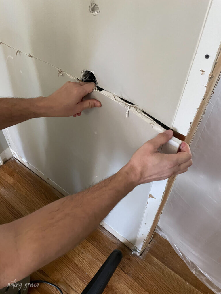 Gently pull away drywall to avoid a mess when removing an interior wall