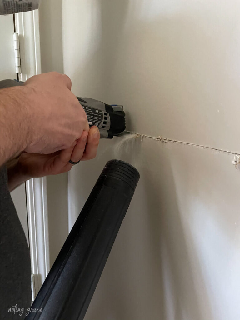 use a shop vac to catch dust when cutting through a wall