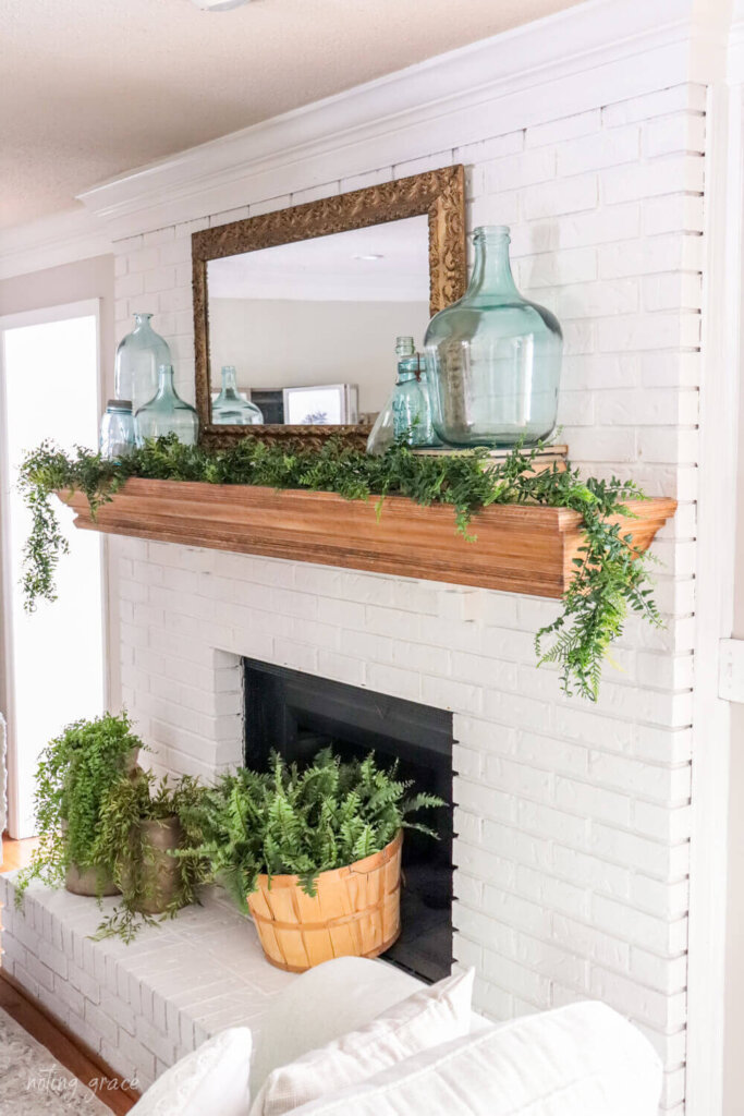 White painted fireplace with blue glass demijohns and greenery styled for summer