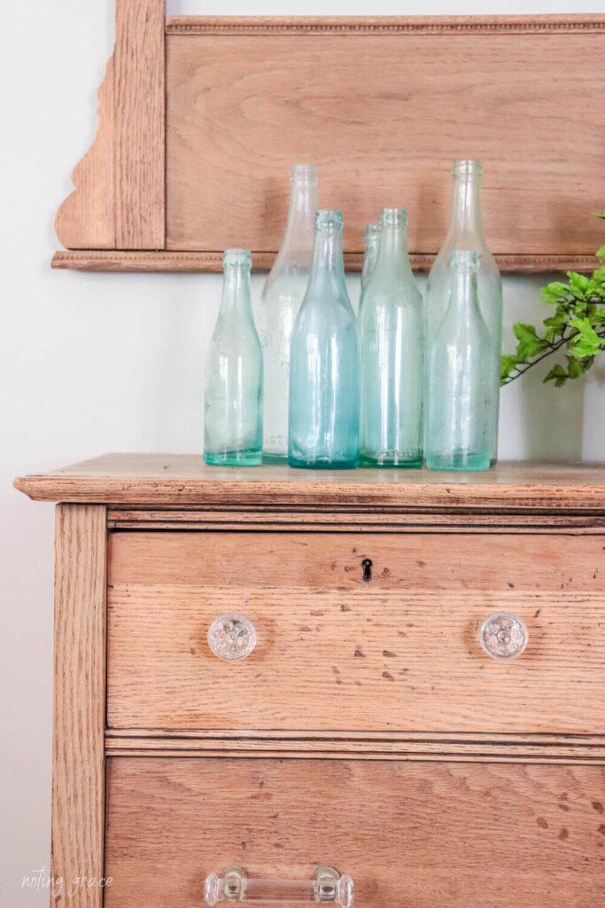 vintage bottles on an unfinished dresser