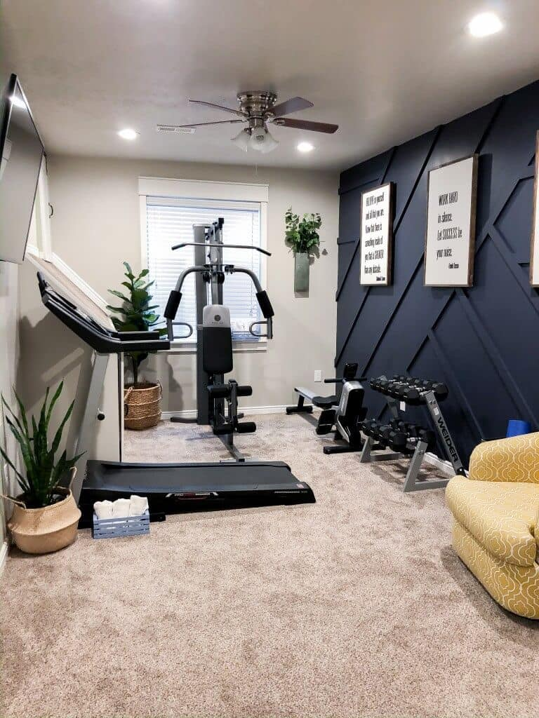 small home gym with treadmill, carpet and navy blue accent wall and yellow chair