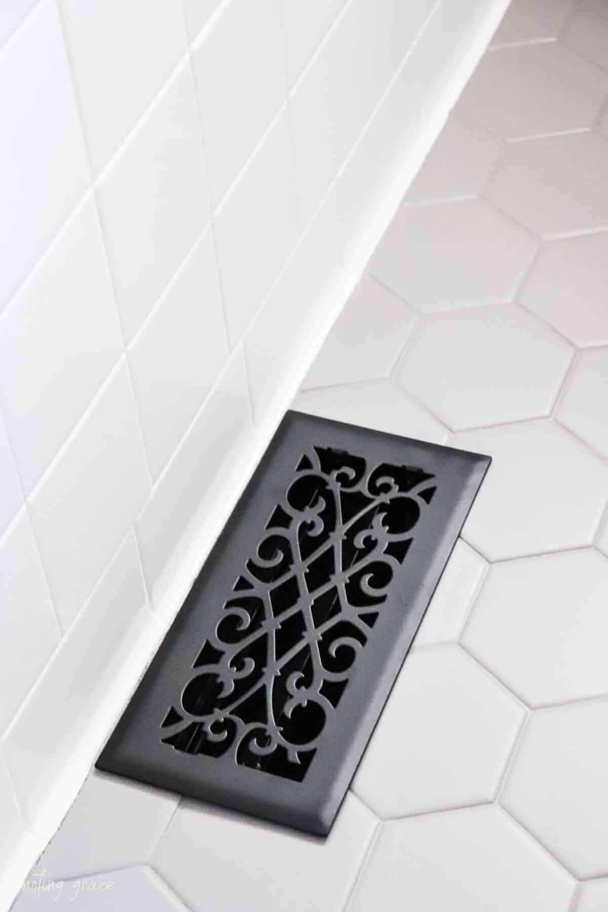 Black floor vent in gray painted hexagon tiles