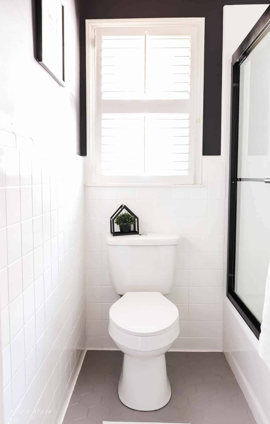 Changed bathrooms tiles for $150 bucks  with White painted wall tiles, gray painted hexagon bathroom flooring and white toilet with black painted walls