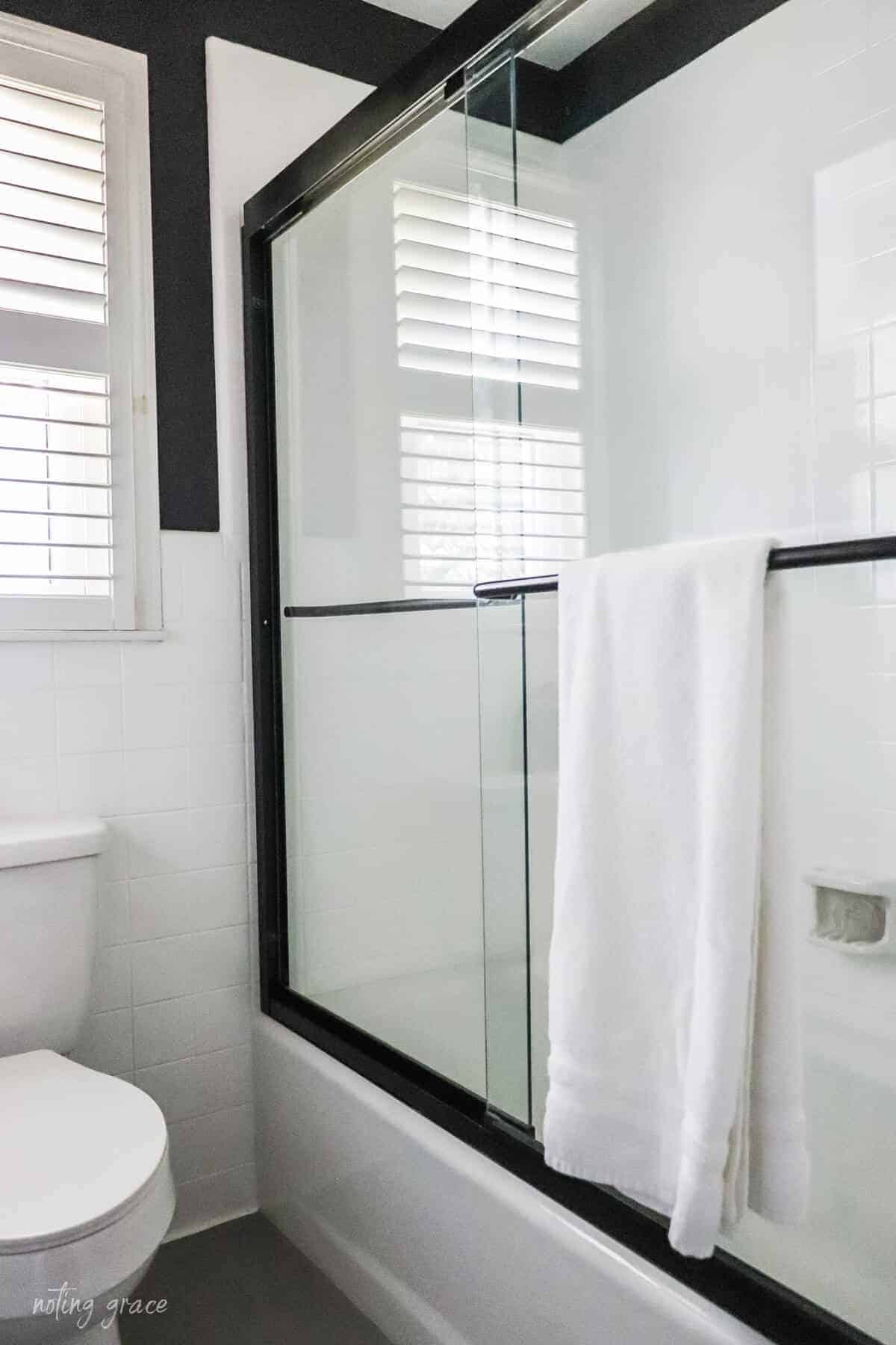 White painted bathtub surround with gray painted floors and black shower doors