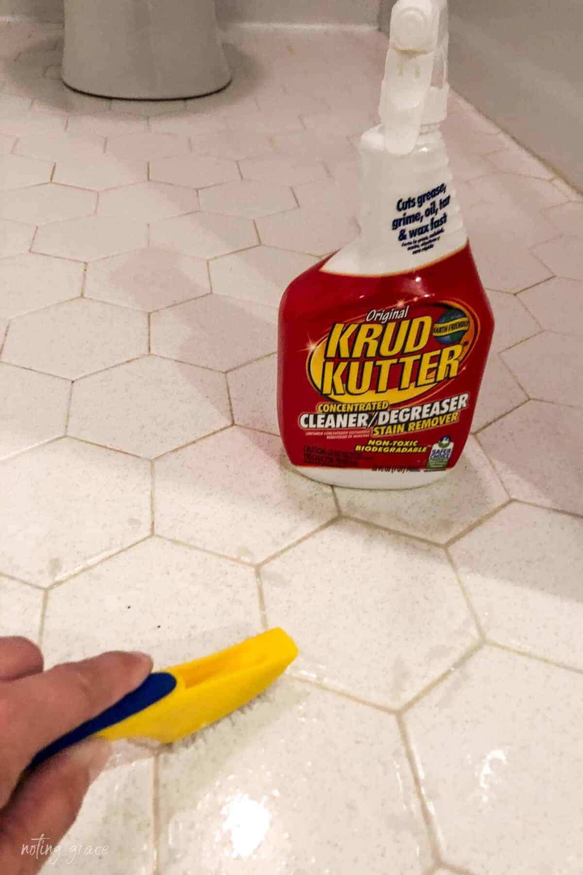 scrubbing hexagon floor tile grout using Krud Kutter cleaner and scrub brush