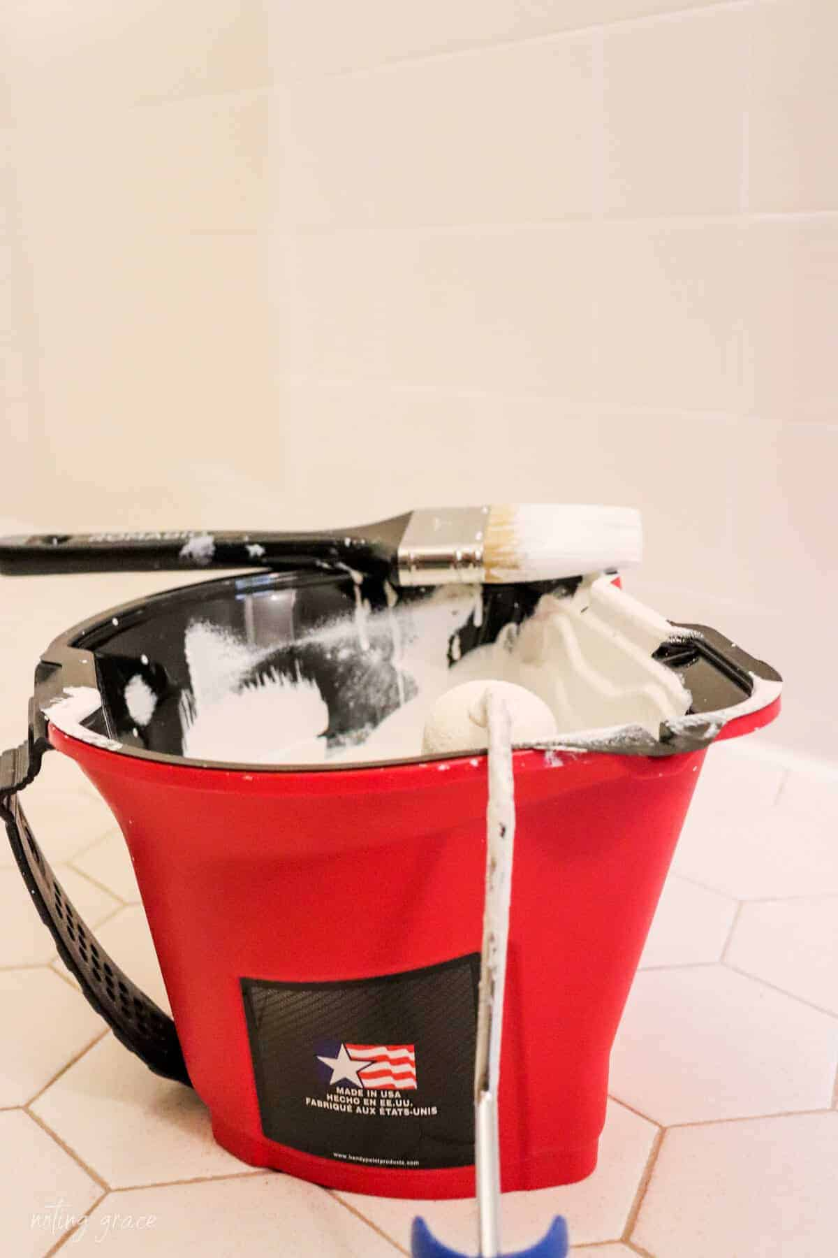 red paint pail filled with white paint, paint brush and roller