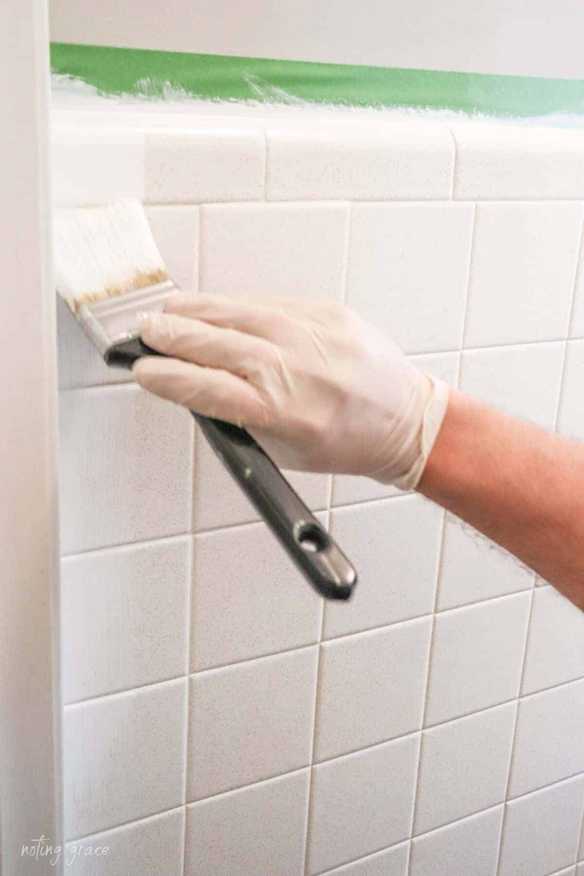 hand painting wall tile using a black handled brush