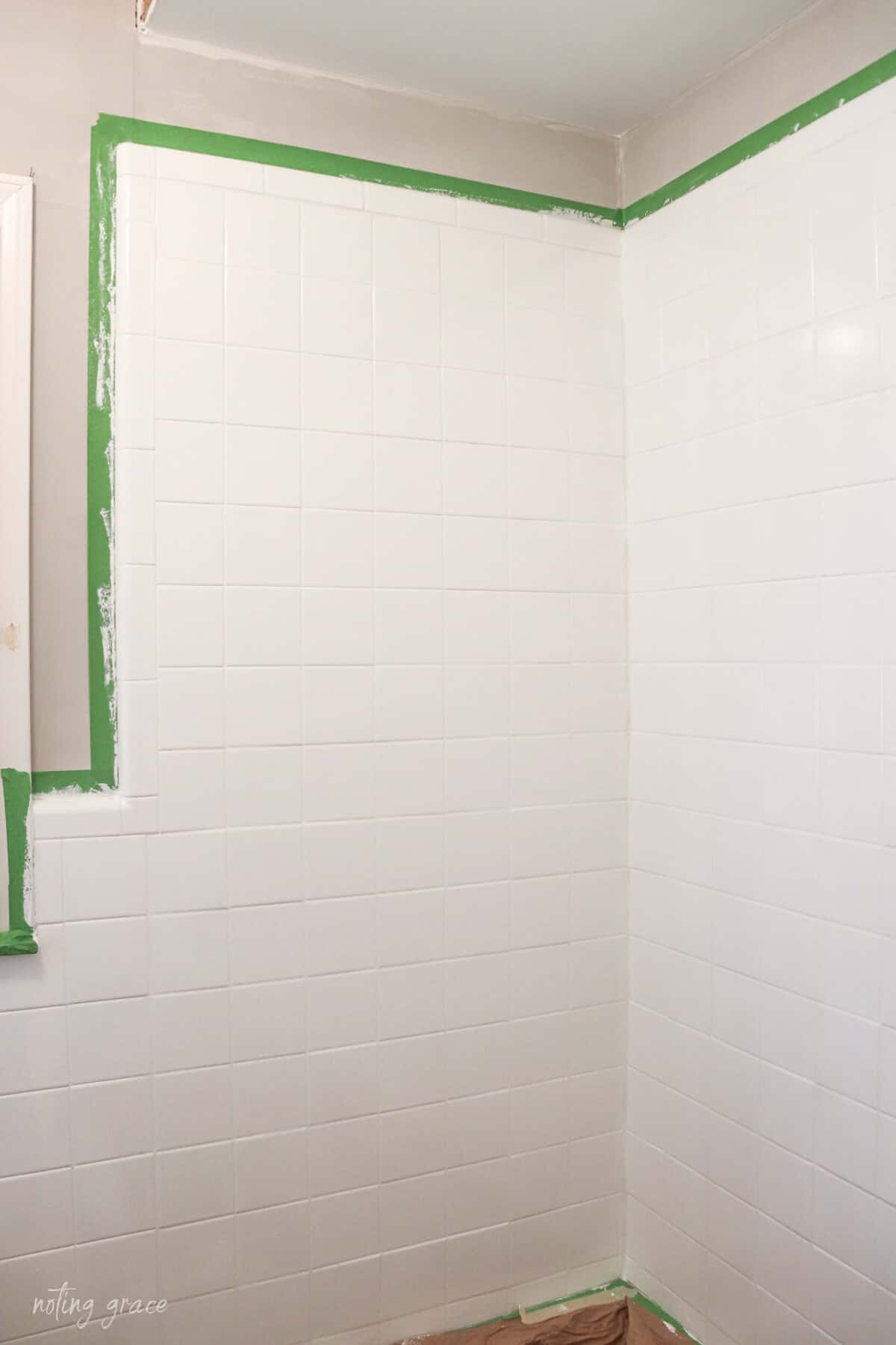 taped off shower surround with painted bathroom wall tile