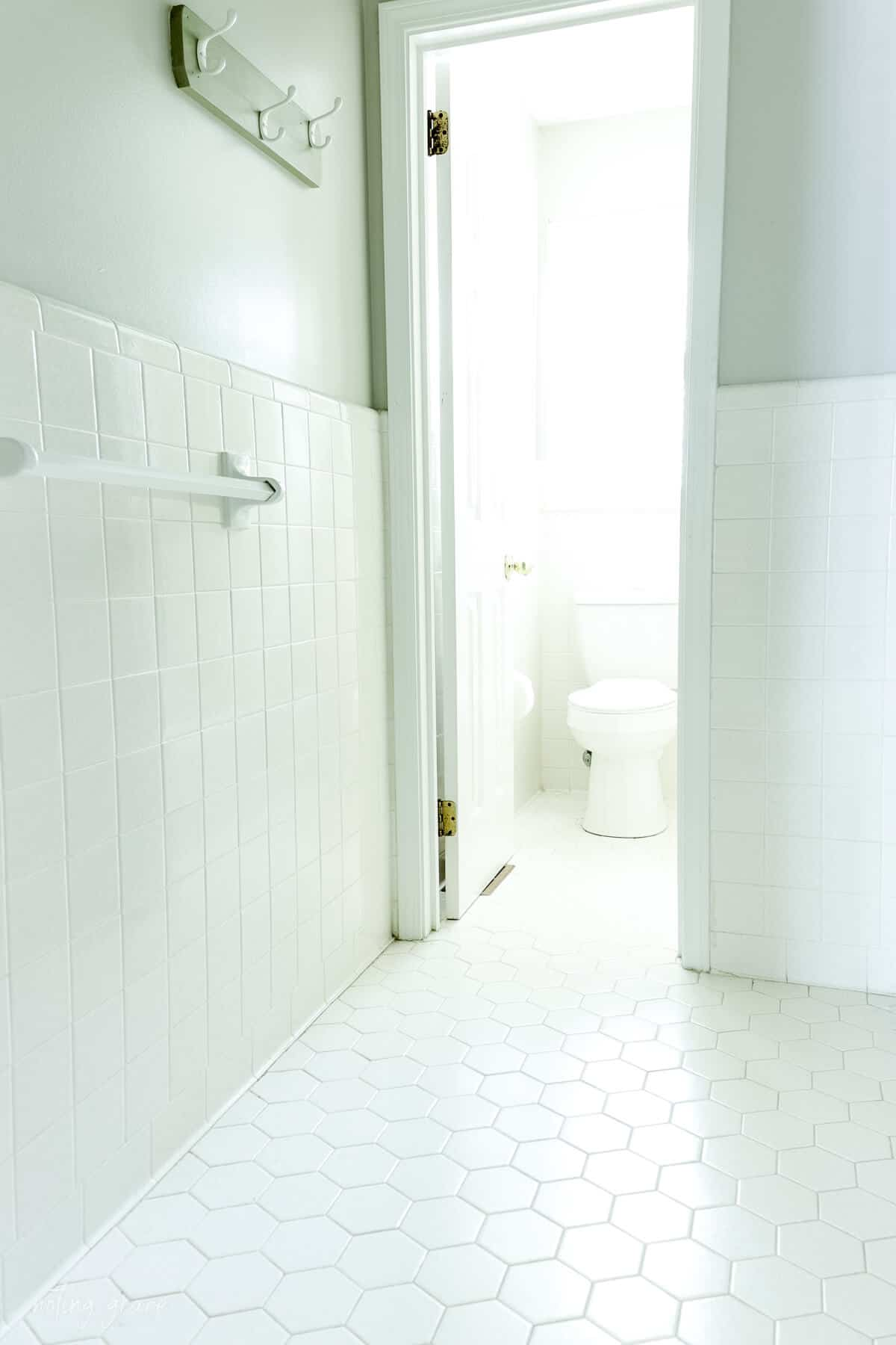 80s style bathroom with white speckled tiled walls and hexagon tiled floor.