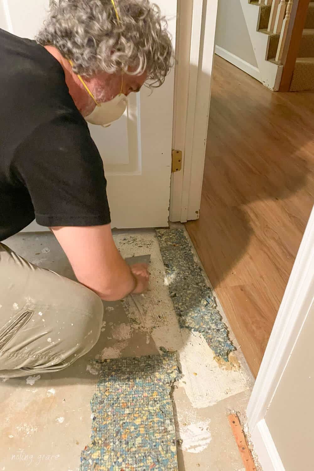 man with gray curly hair wearing a breathing mask scraping carpet pad remnants from concrete basement floor