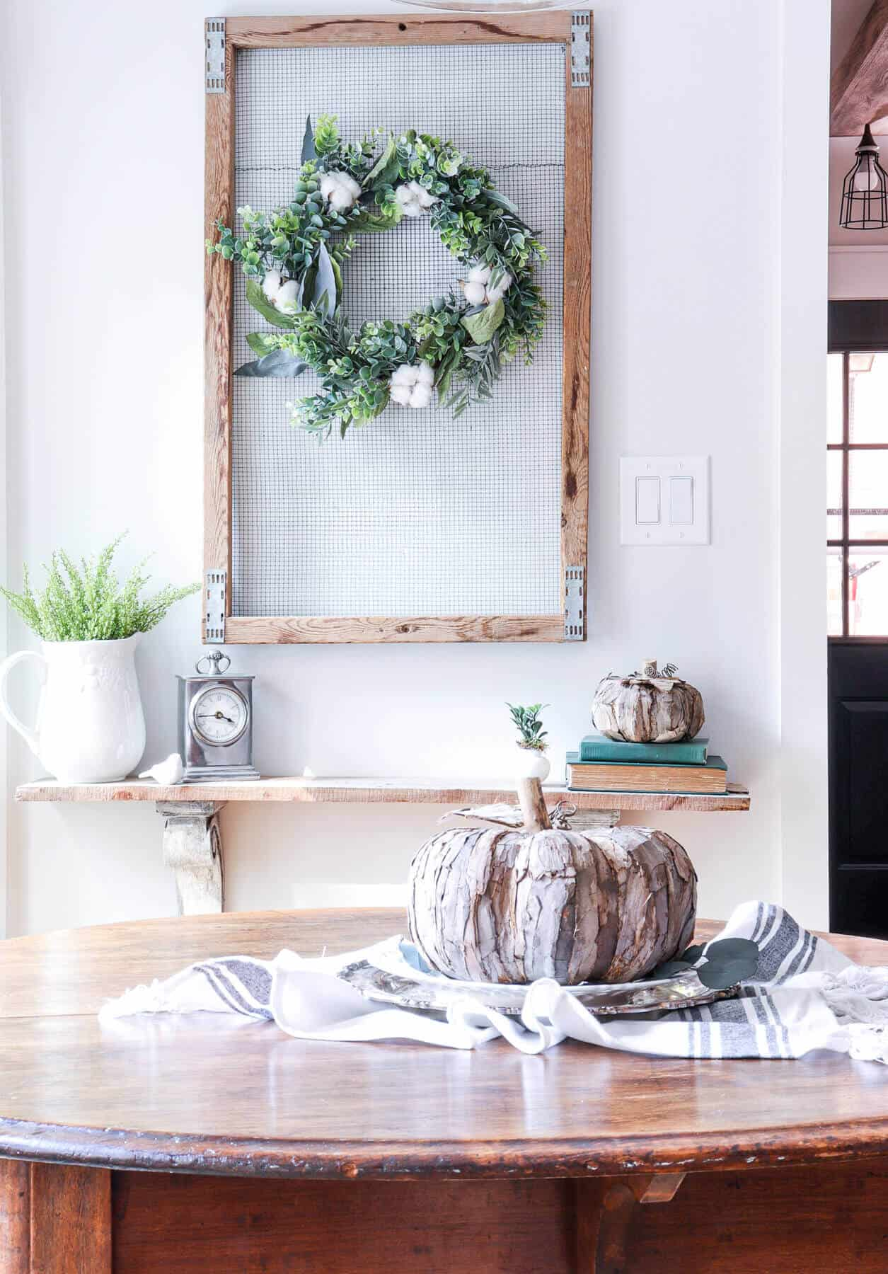 Simple fall wreath with eucalyptus and cotton hanging above a small shelf