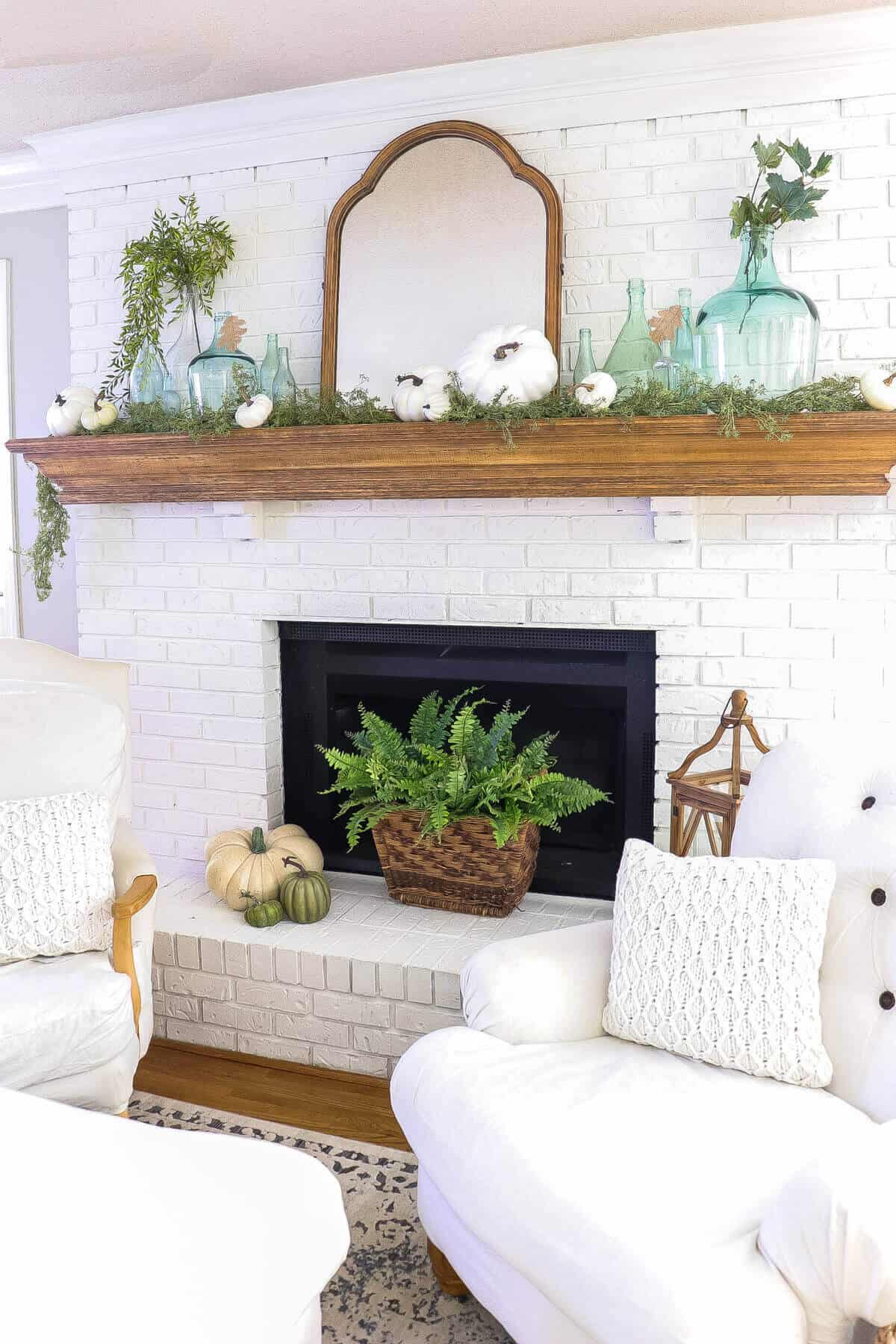fall mantel with blue bottles and white pumpkins