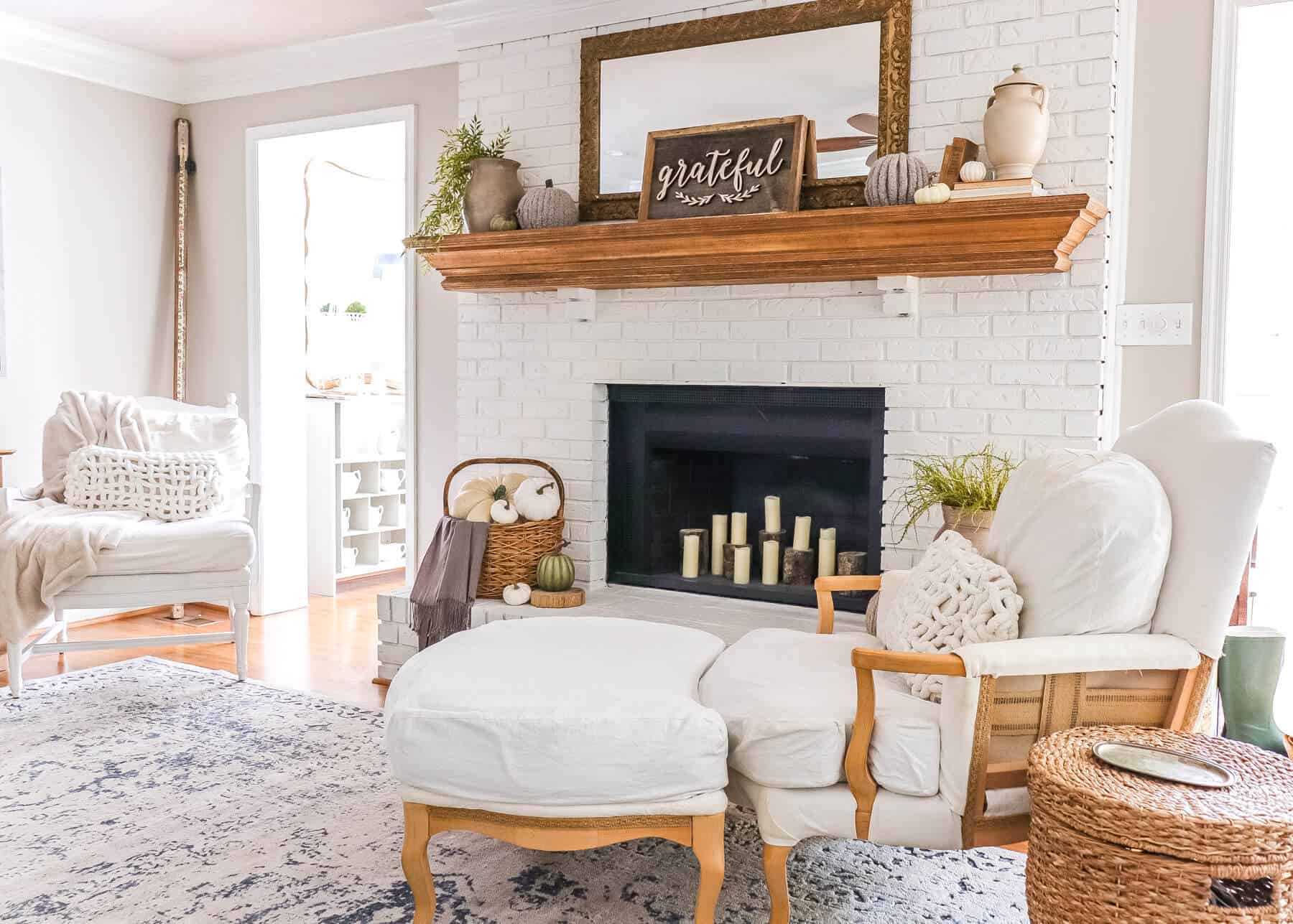fall mantel decor with candles in the fireplace