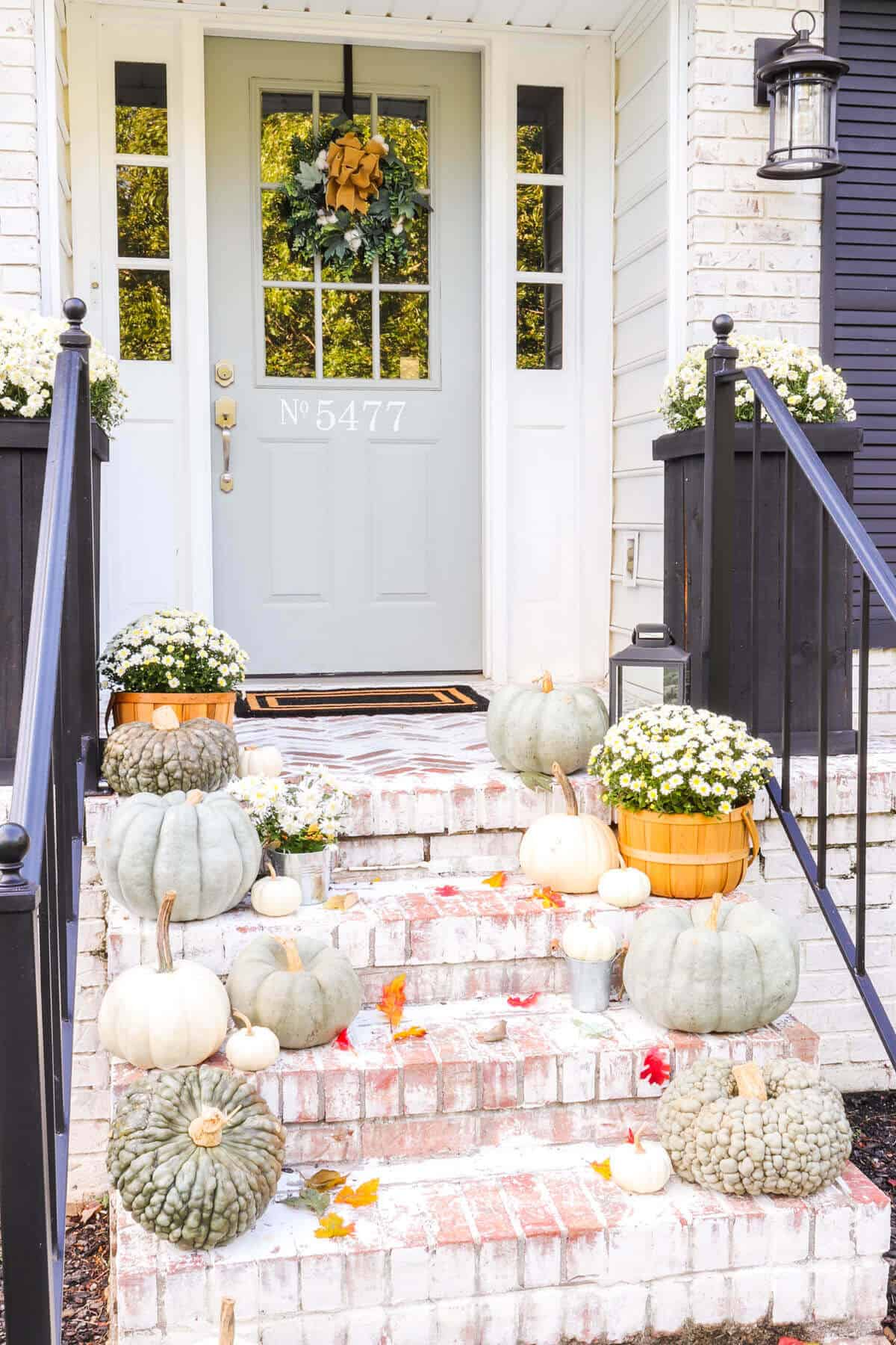Fall front porch with heirloom pumpkins and mums on brick steps
