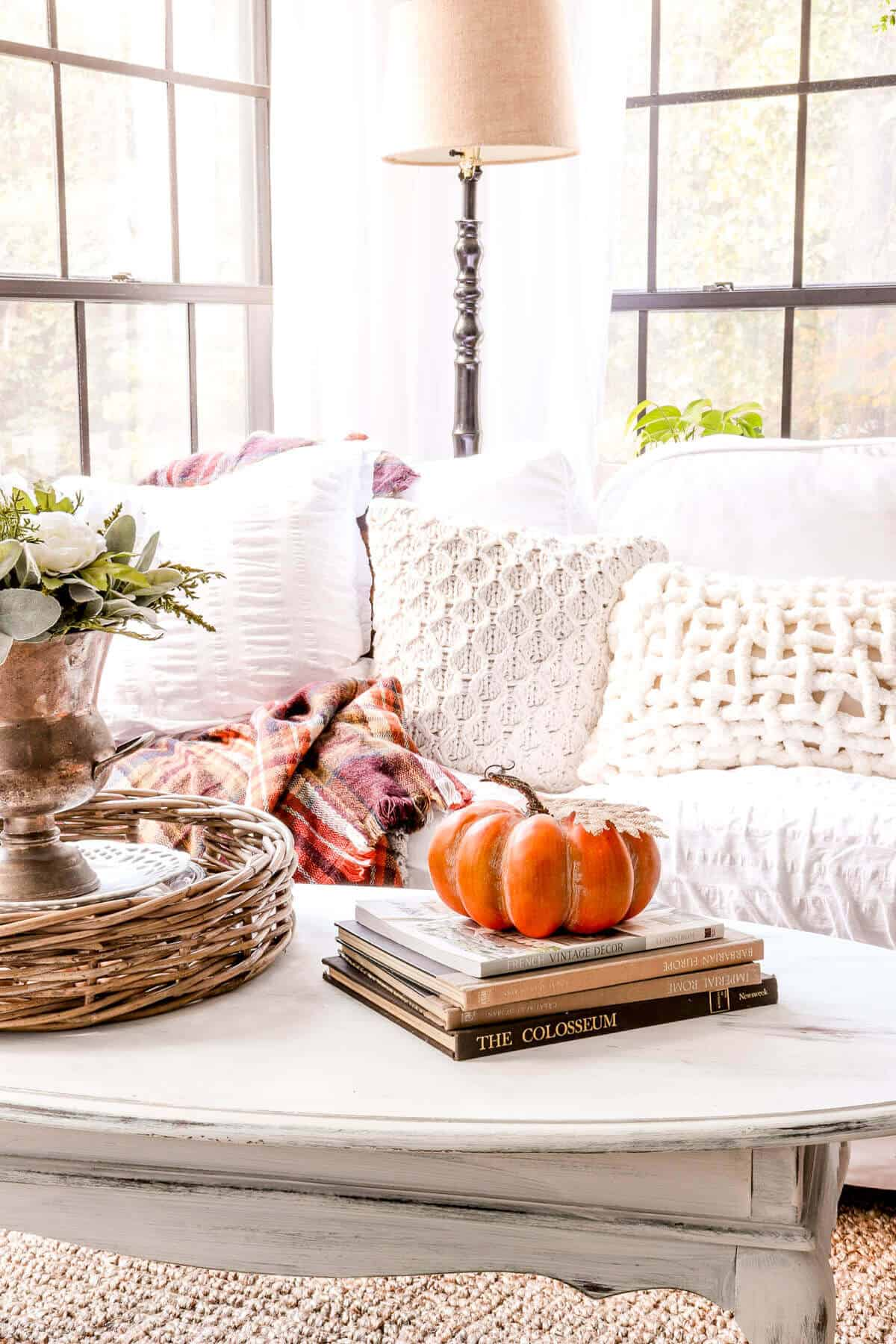 orange plaid blanket with knit pillows on a couch with a coffee table in front with an orange pumpkin