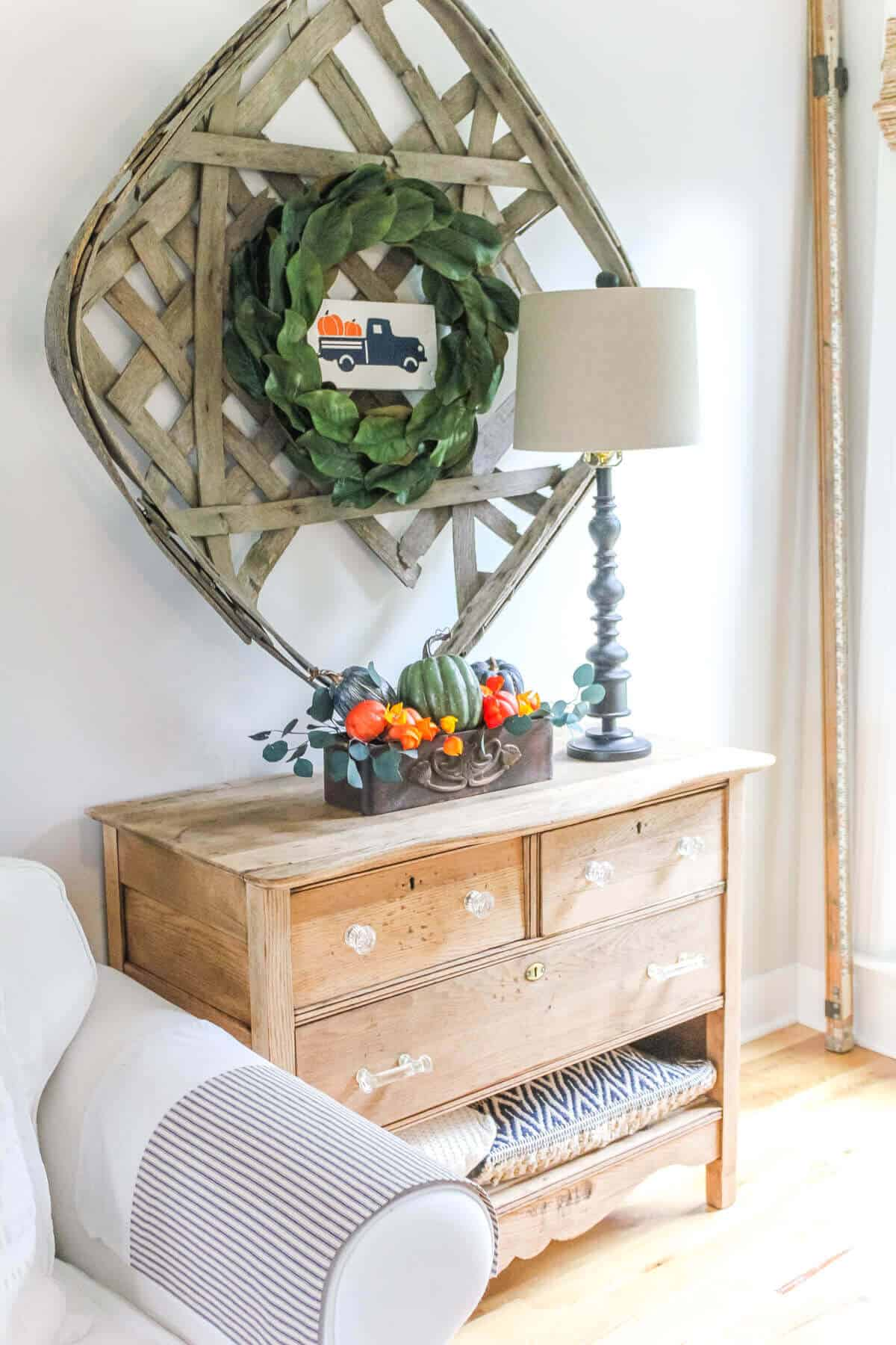 Magnolia leaf wreath with a painted wooden sign showing a vintage truck filled with pumpkins hanging on a tobacco basket