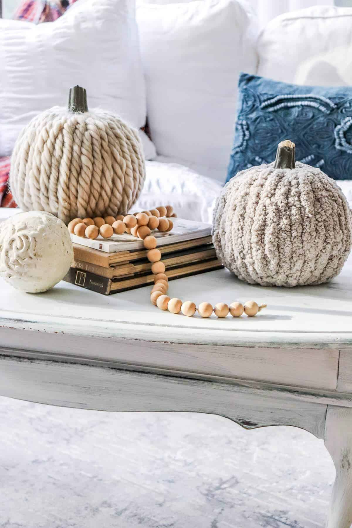 yarn covered pumpkins with a wood bead garland sitting on a stack of books