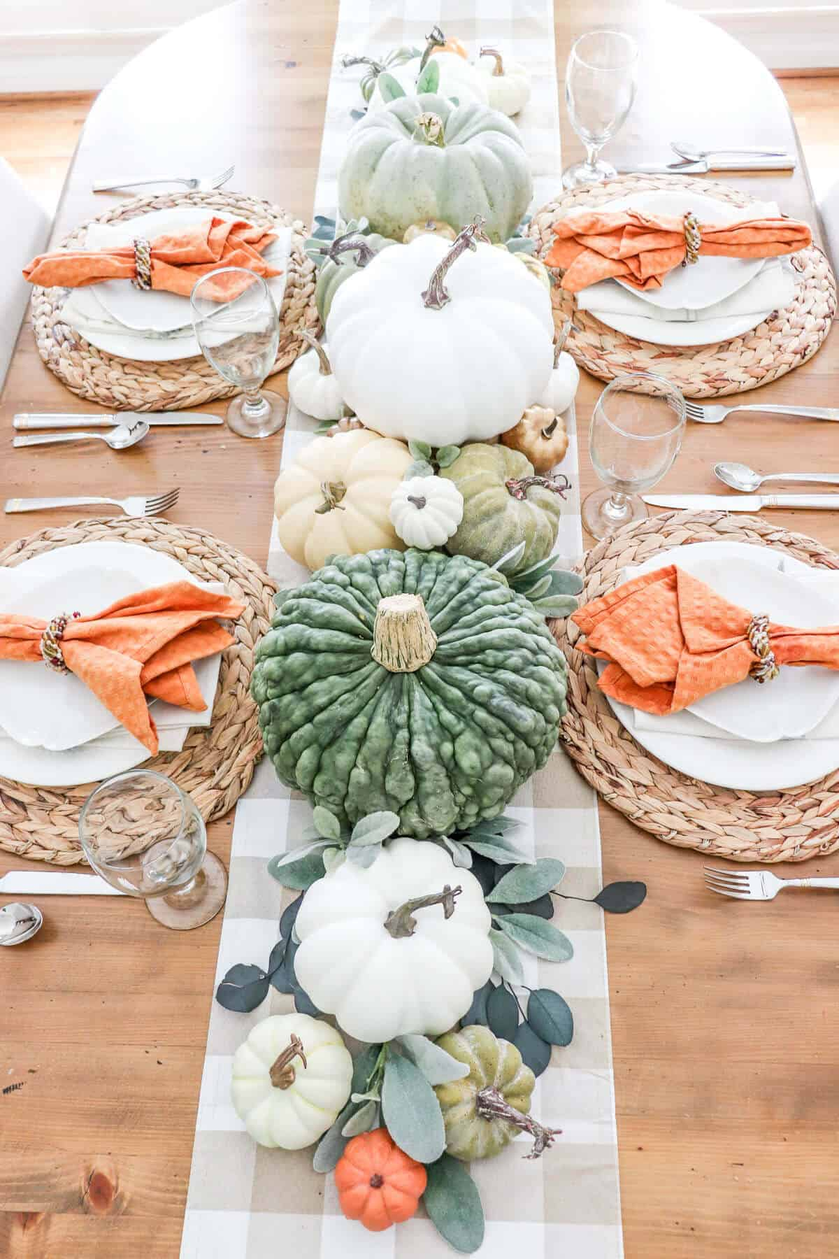 fall table setting of rattan platelets, white plates and orange napkins with white, green and orange pumpkins  as a centerpiece