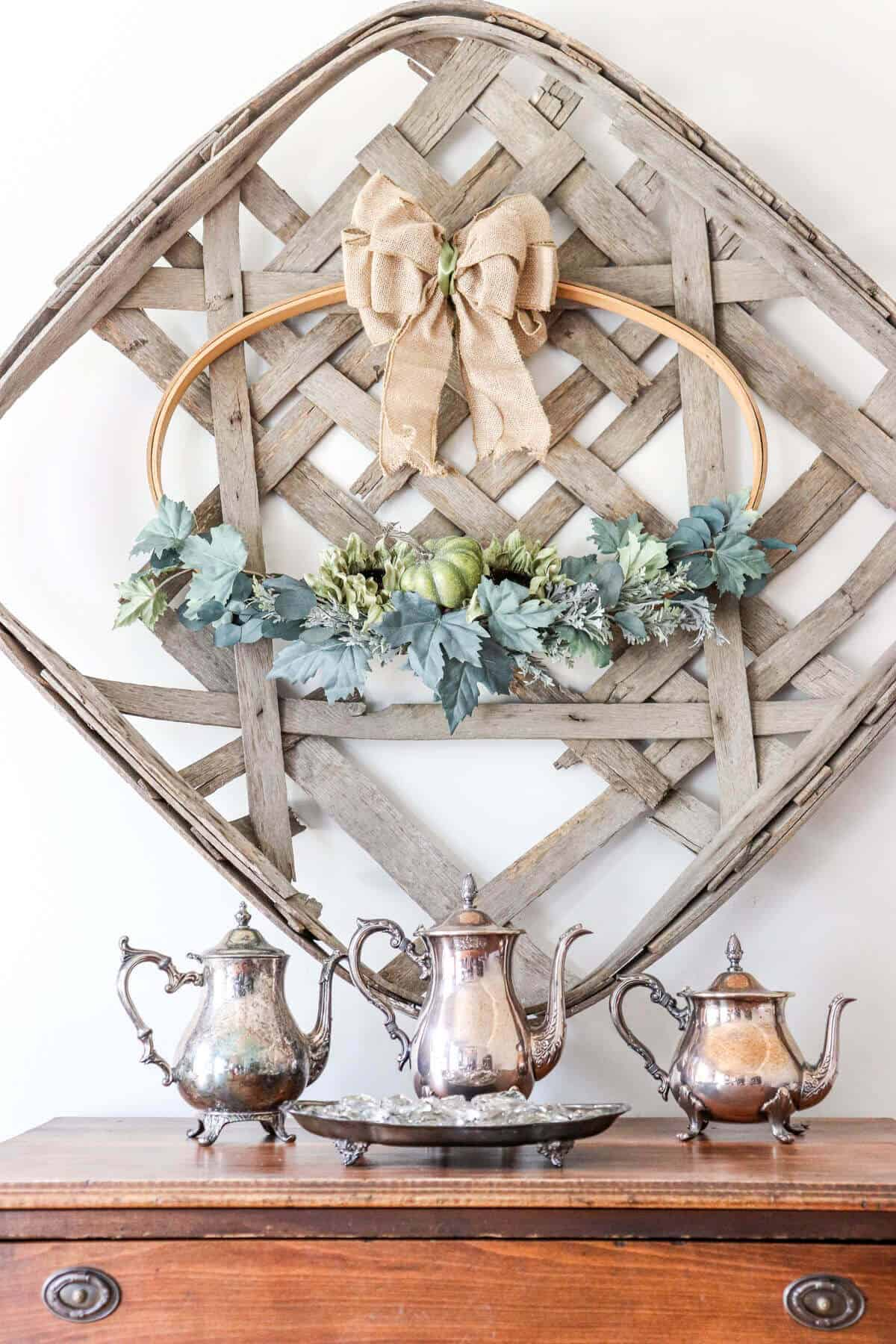 Tobacco basket with hoop wreath decorated for fall hanging above a wood table with vintage tarnished silver pitchers.