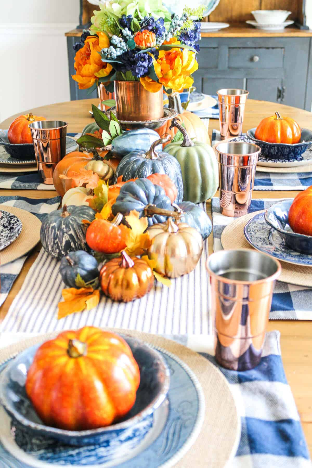 orange and blue fall tablescape with copper glasses and blue plates