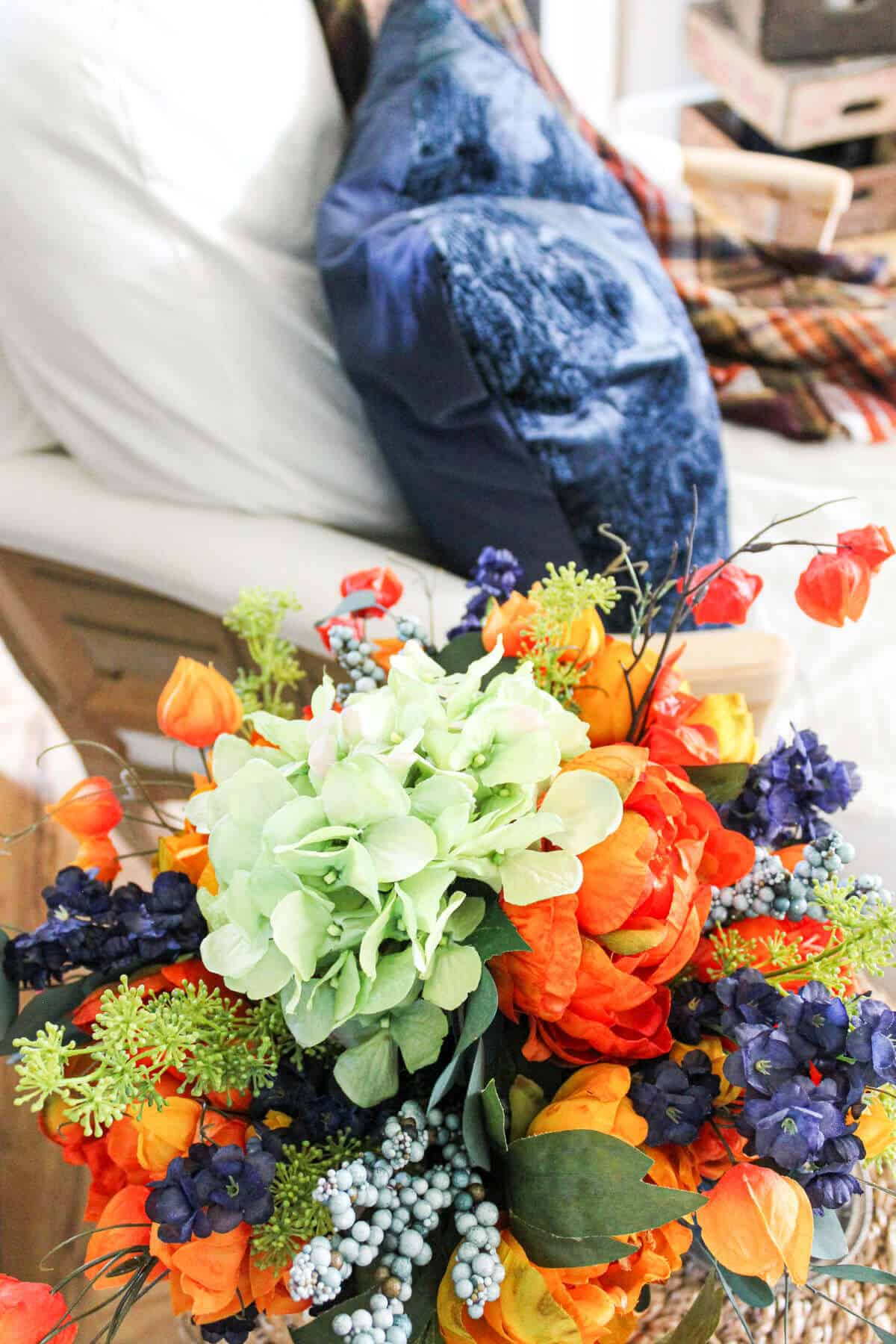 faux fall floral arrangement with green hydrangeas and blue and orange flowers
