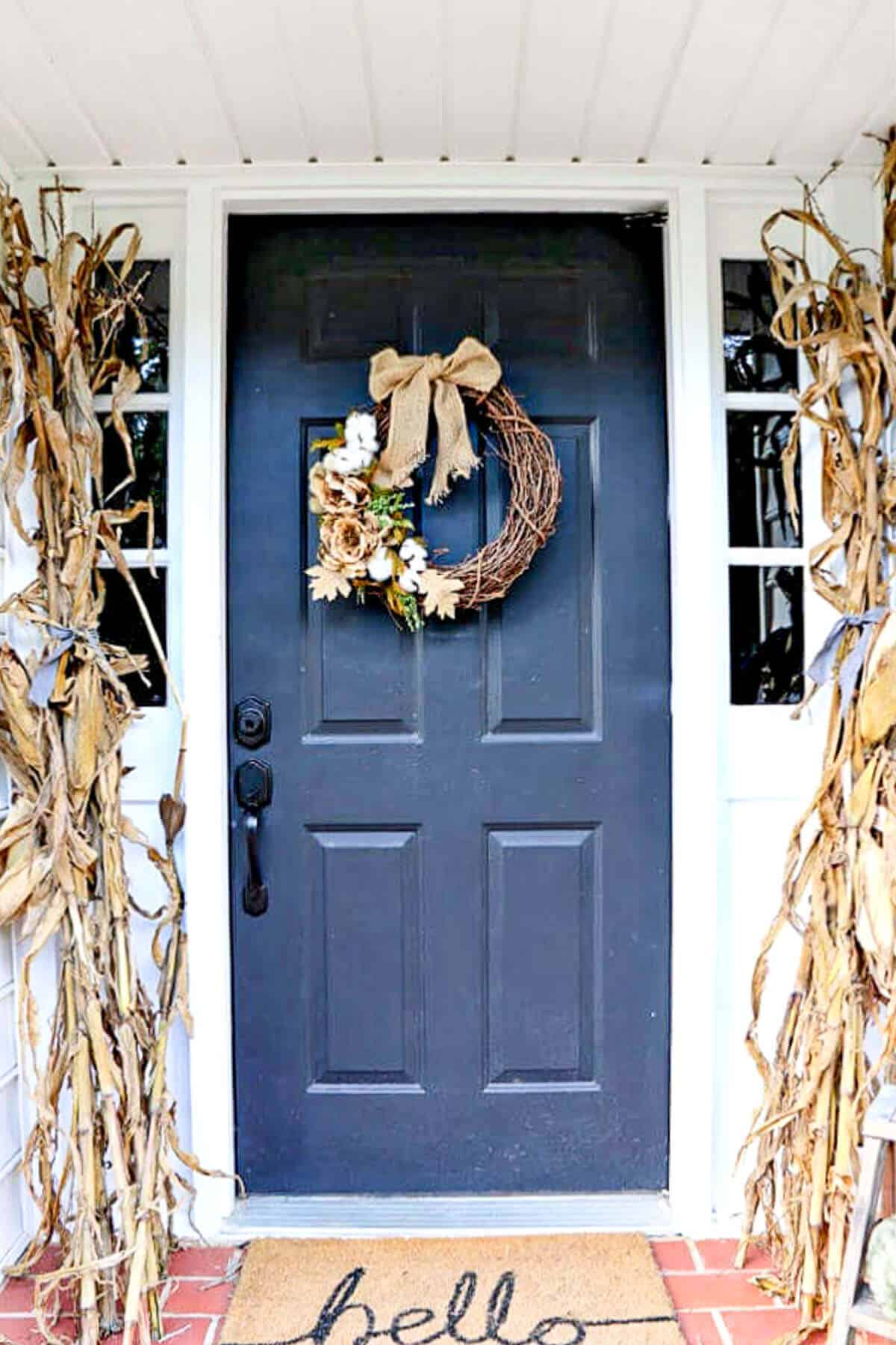Black door decorated for fall with cornstalks and a fall wreath