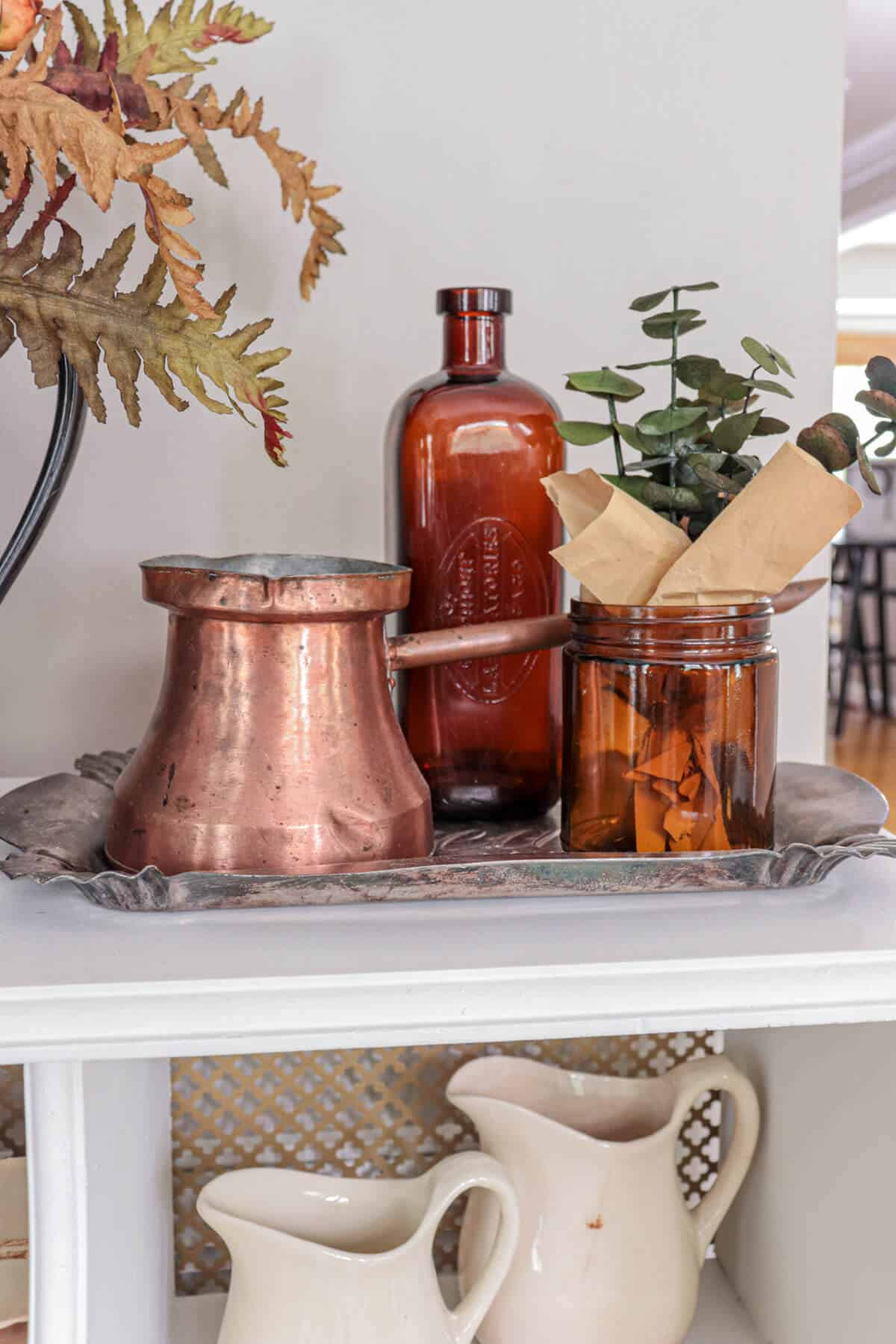 amber bottles and copper elements sitting on a tarnished silver tray