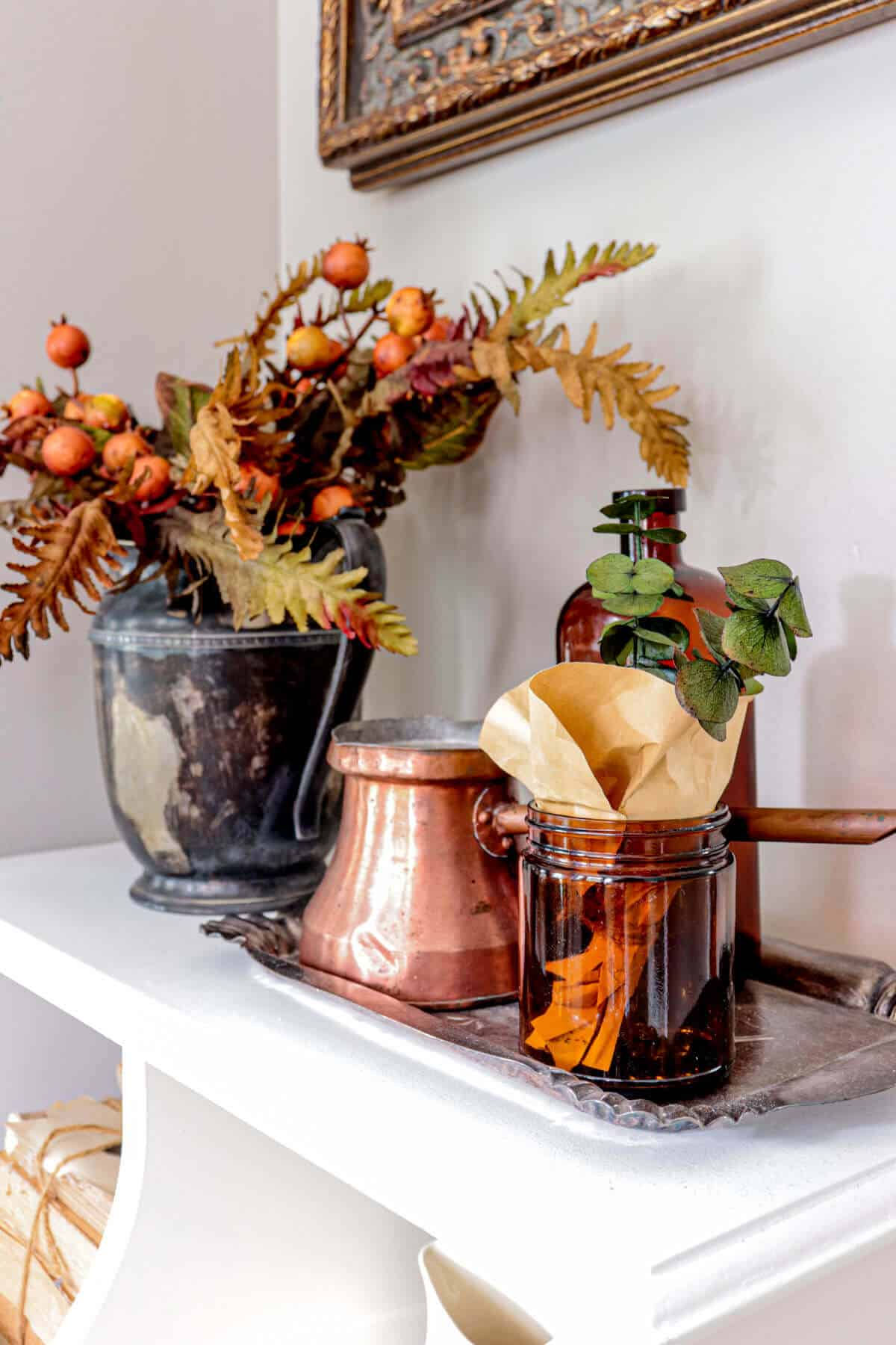 tarnished silver pitcher filled with orange fall greenery next to amber bottles and copper elements