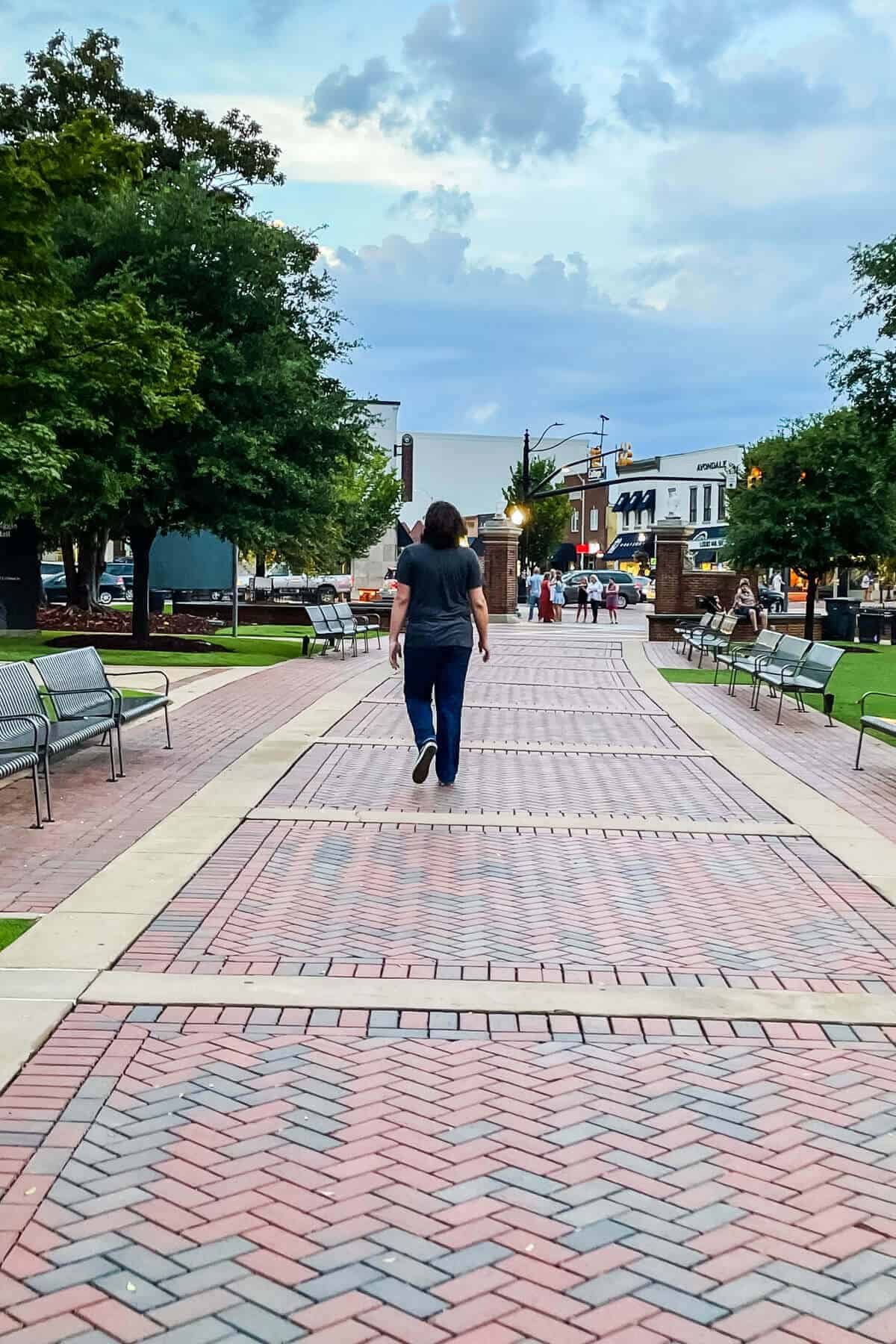young man walking on brick pavement on a college campus