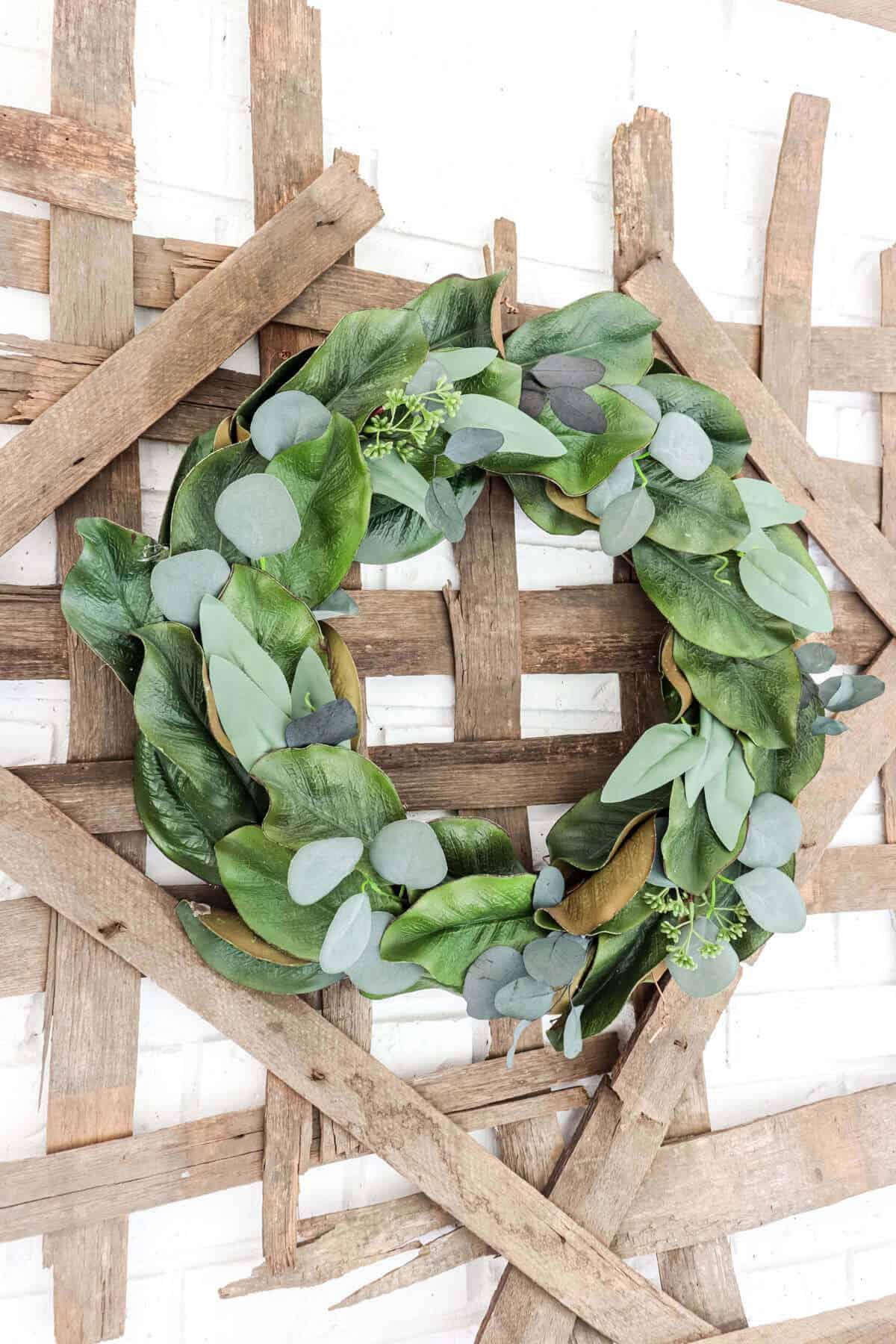 magnolia leaf wreath with eucalyptus hanging on a tobacco basket