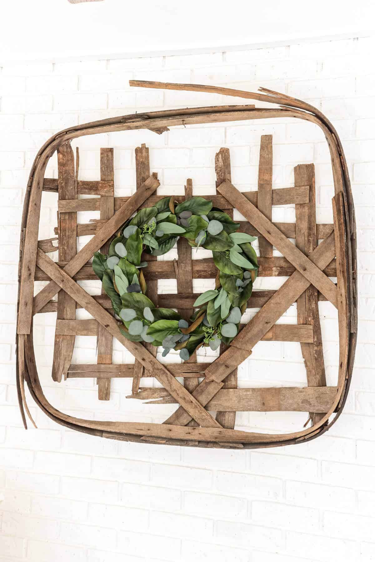 tobacco basket with magnolia and eucalyptus leaf wreath hanging on it.