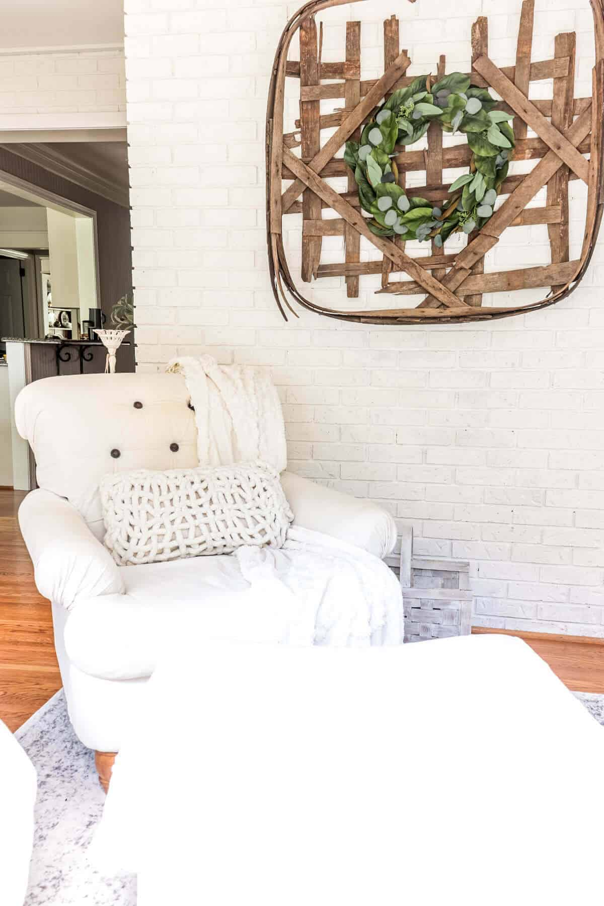 white armchair next to a white lime washed brick wall with a tobacco basket and wreath hanging on the wall
