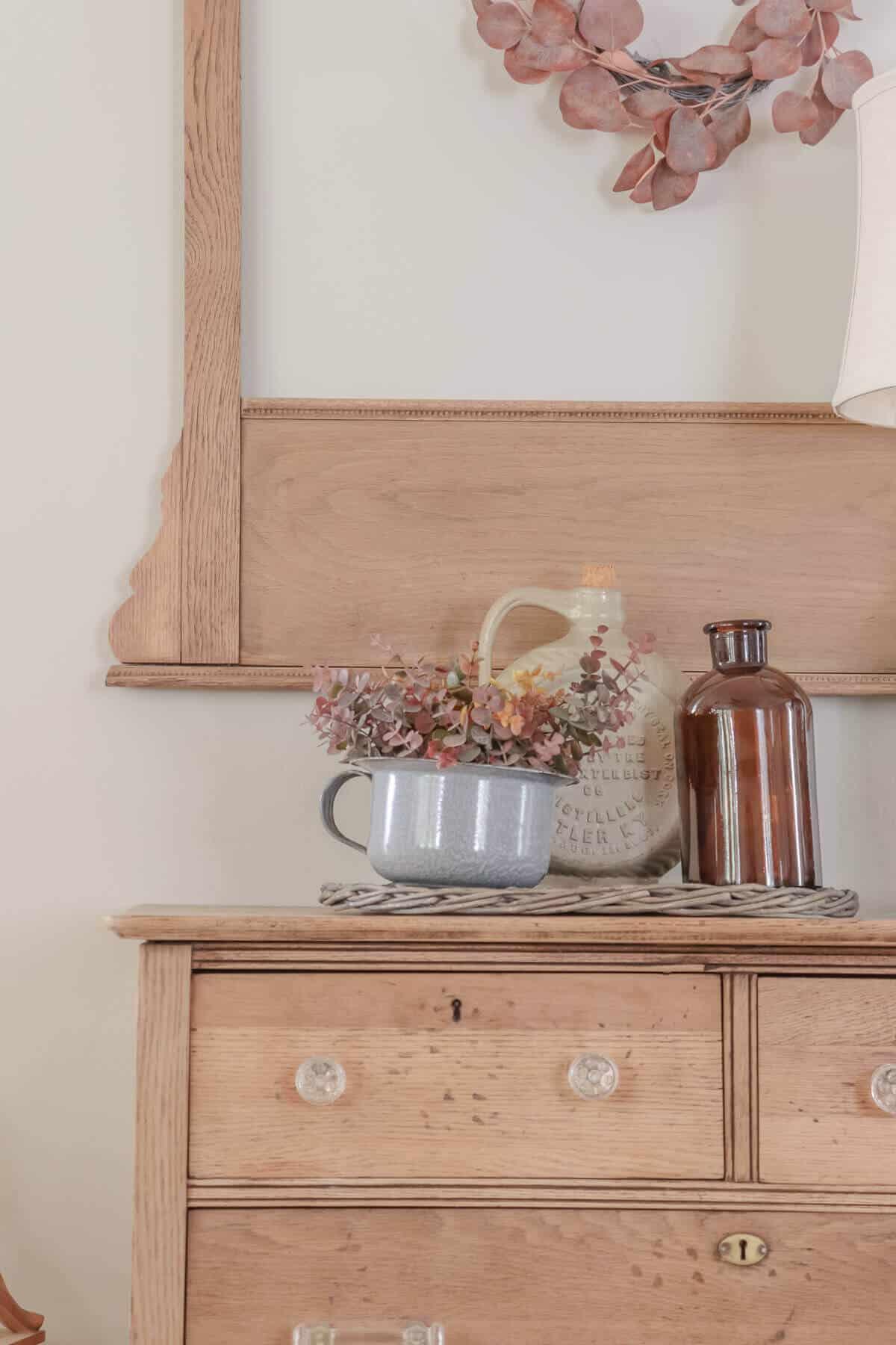 vintage crocks, amber bottles and gray spatterware in a fall arrangement