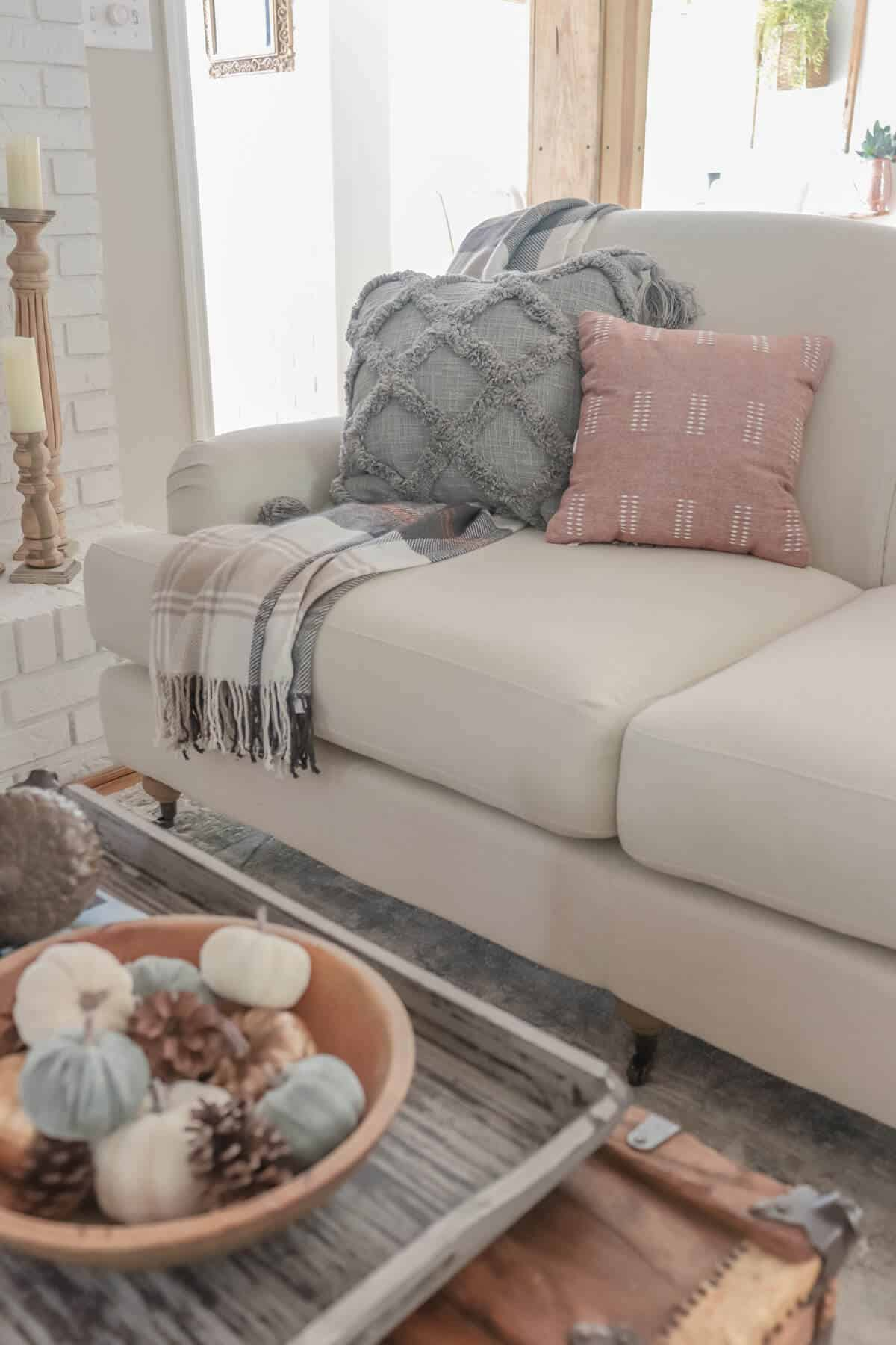 gray pillow with plaid throw
