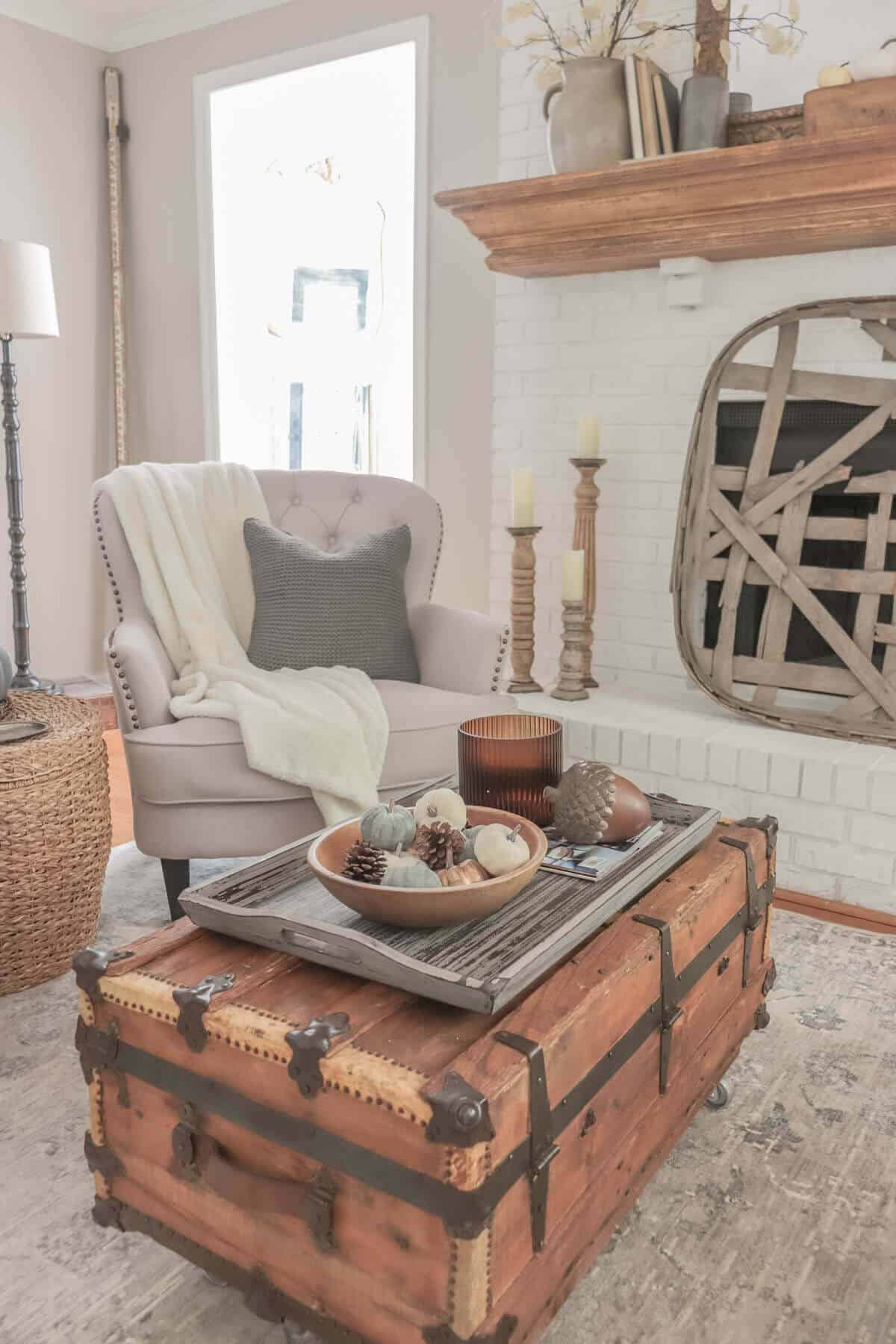 white fireplace painted with Romabio masonry flat with a tobacco basket as a screen and a fall decorated mantel with old books and crocks