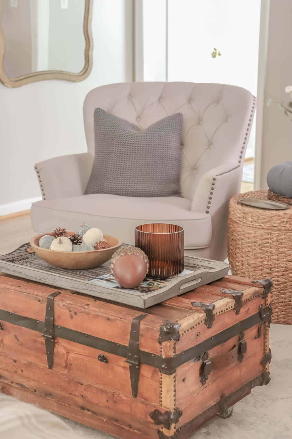 armchair with gray pillows with vintage wooden crate as a coffee table decorated for fall