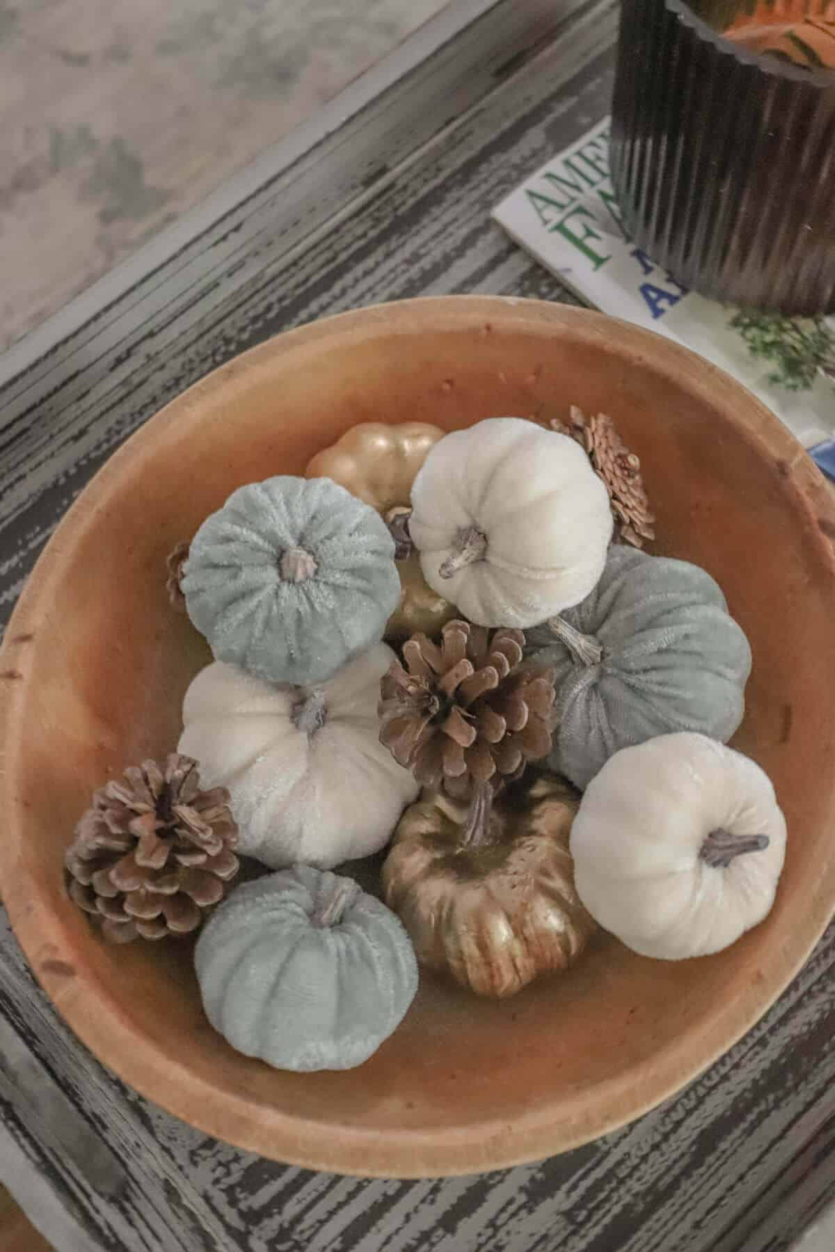 wooden munising bowl filled with cream, gray, and copper pumpkins and pinecones