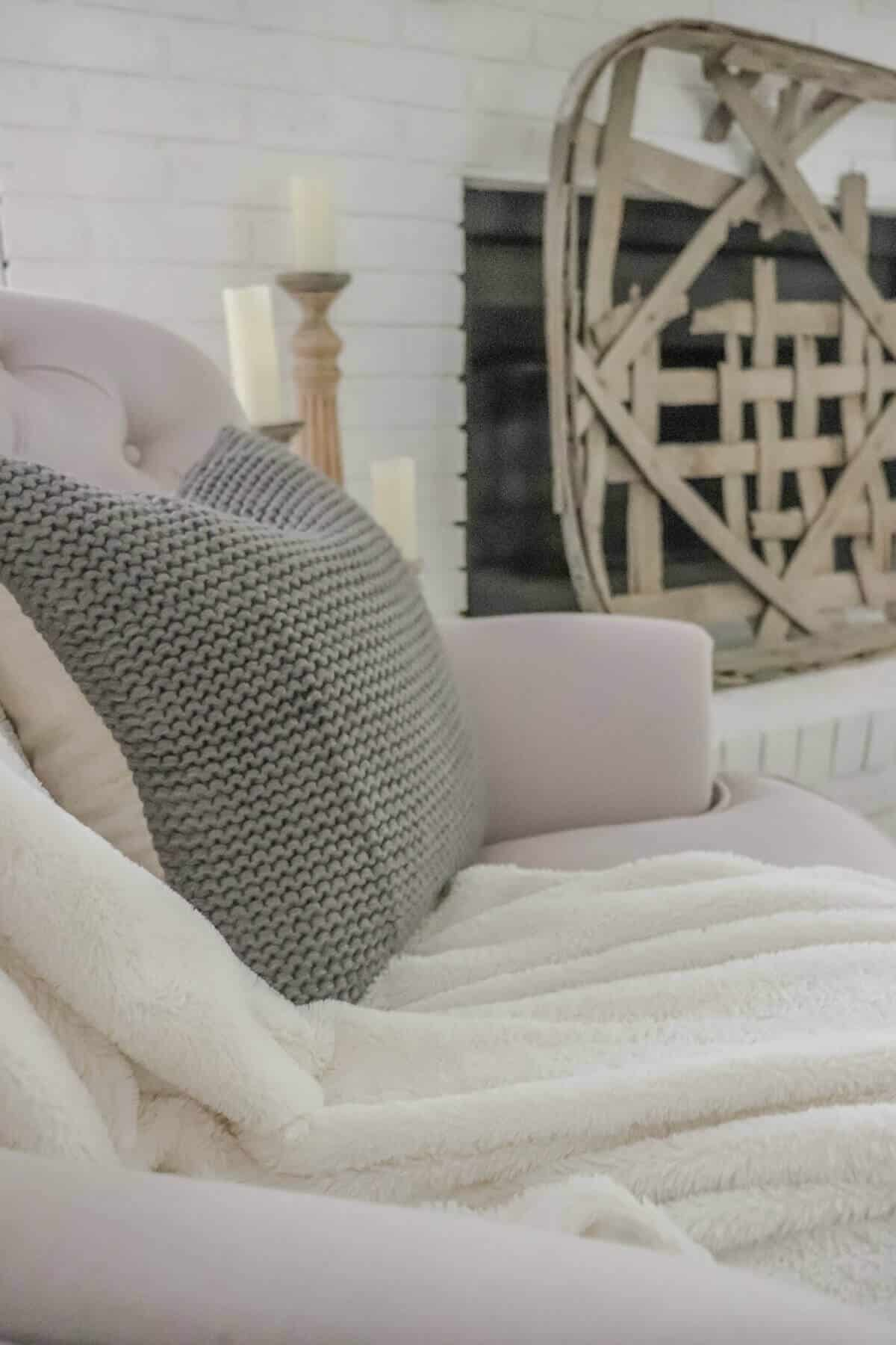 Gray Knit Pillow on armchair next to a white painted fireplace with a tobacco basket as a screen