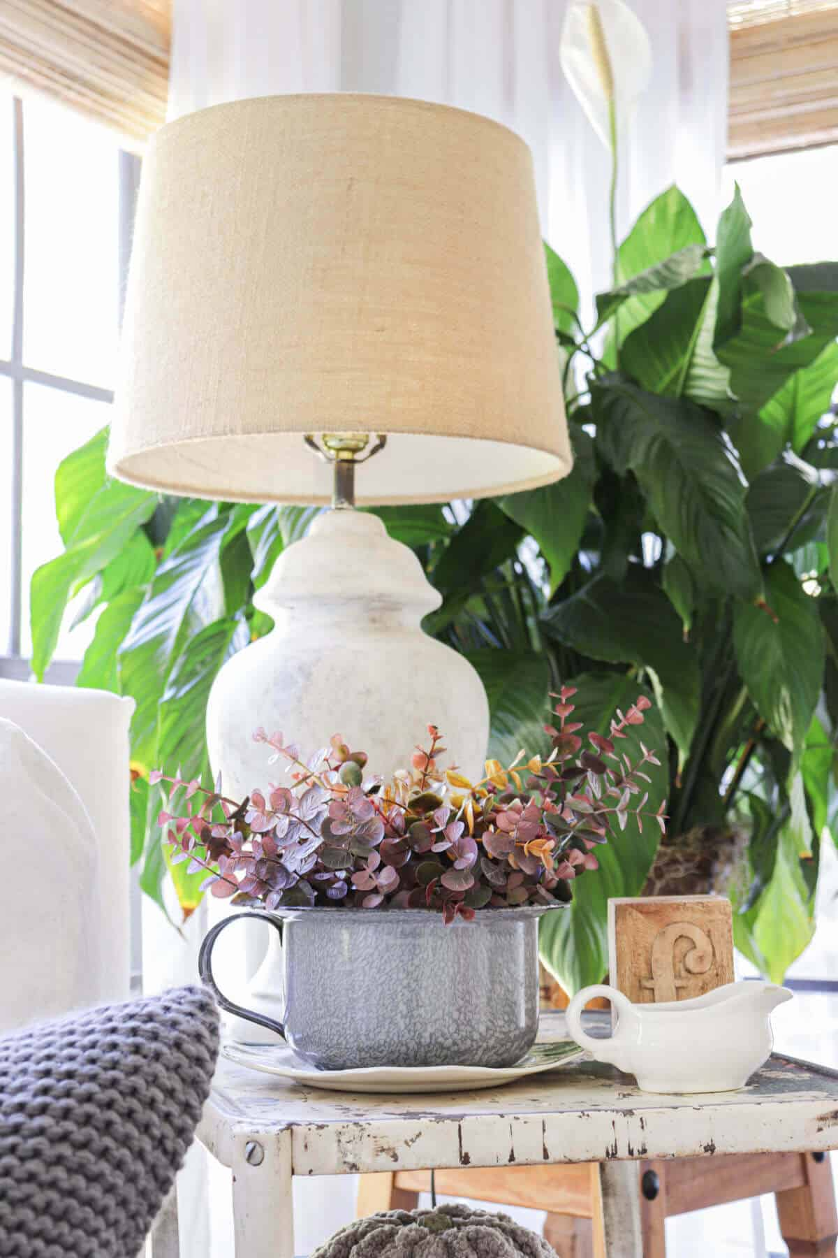 white painted lamp with burlap lamp shade sitting on a metal table with a gray splatterware bowl filled with Burgundy eucalyptus