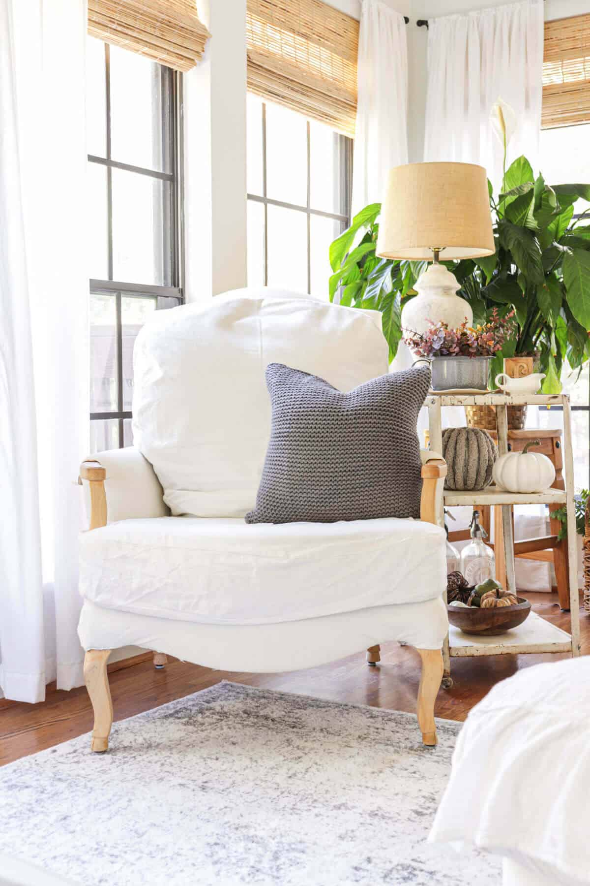 white armchair with a gray knit pillow,
