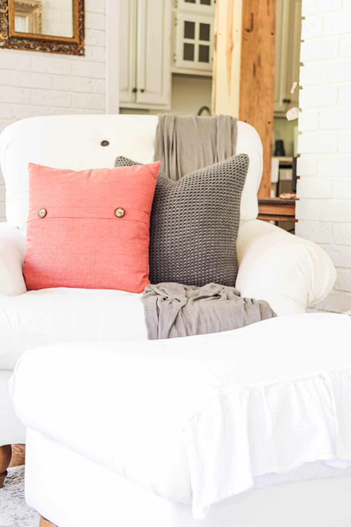 white armchair with a gray knit pillow, gray throw blanket and orange throw pillow with 2 wooden buttons.